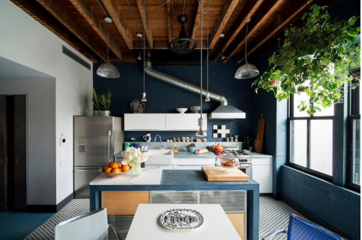In the kitchen, Mr. Salasky exposed the ceiling joists and stripped the walls down to brick, which he painted a deep blue, and added a plywood-covered wall with windows