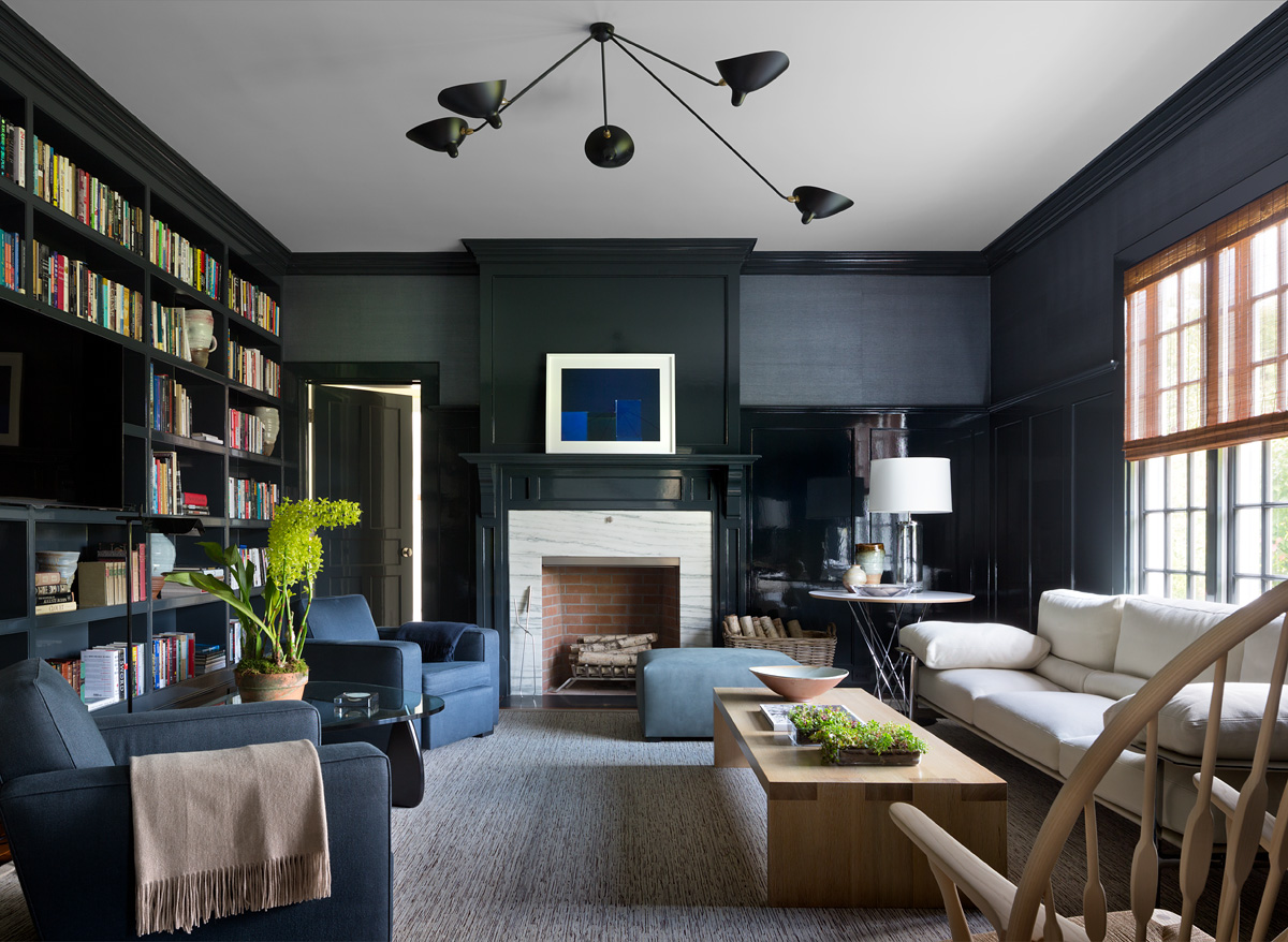 A dark and cozy library with grasscloth wallpaper and Serge Mouille lighting. Photography by Andrew Frasz.