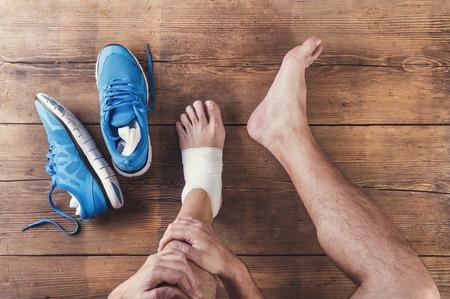 39482245_S_bandage_foot_male_injury+sneakers_gauze_wood_floor_indoor_pain_hurt_injury.jpg