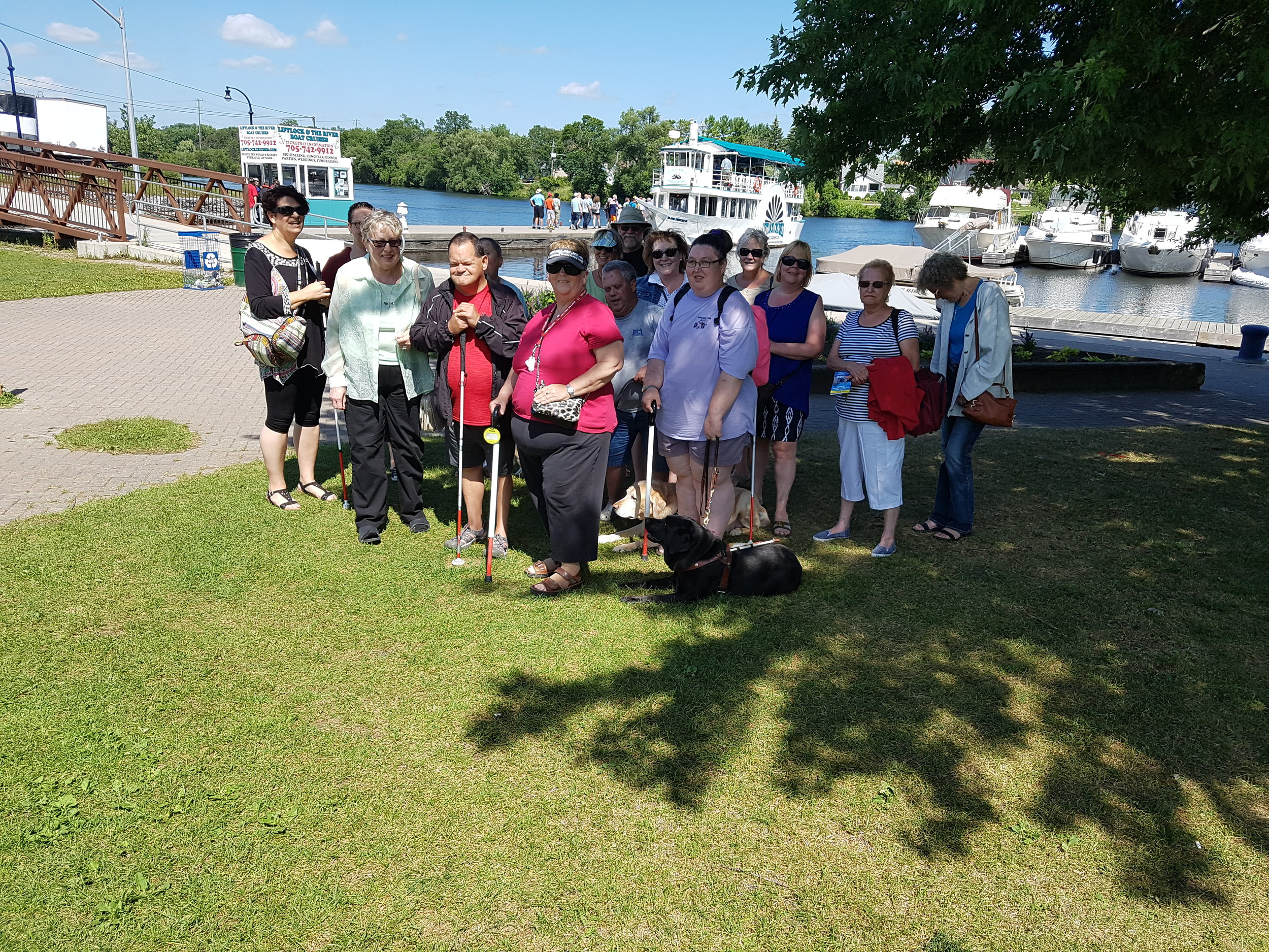 Members and volunteers of the Peterborough chapter standing on the grass in front of little lake and Liftlock Cruises.