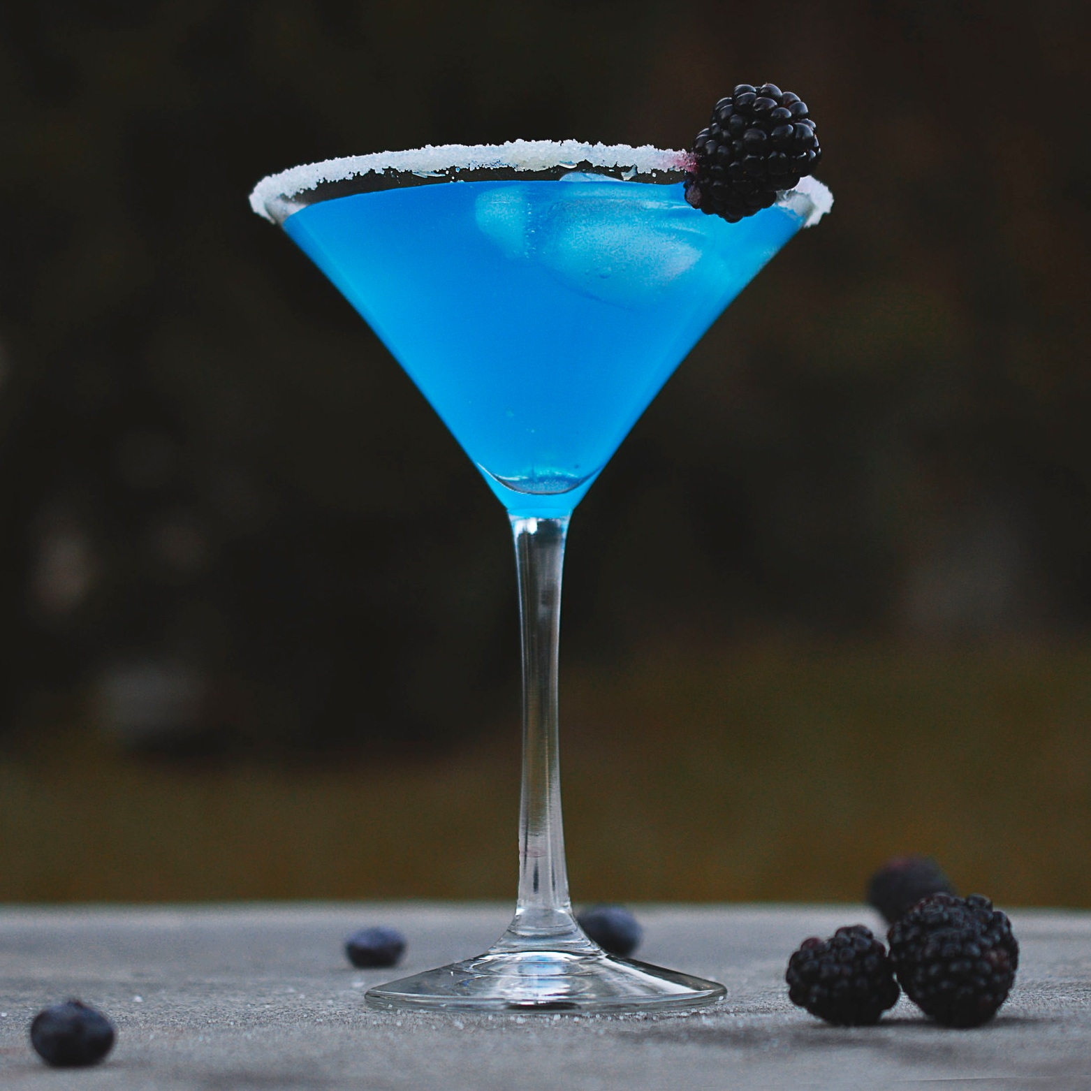 Blue Cocktail in Martini Glass with Blackberry