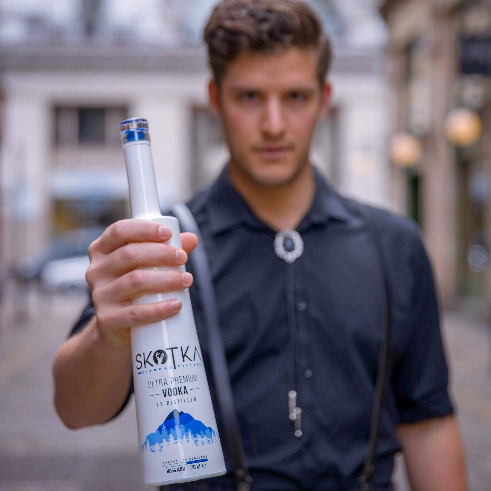 Lady wearing blue dress leaning on bar with bottle of SKOTKA Vodka on the bar