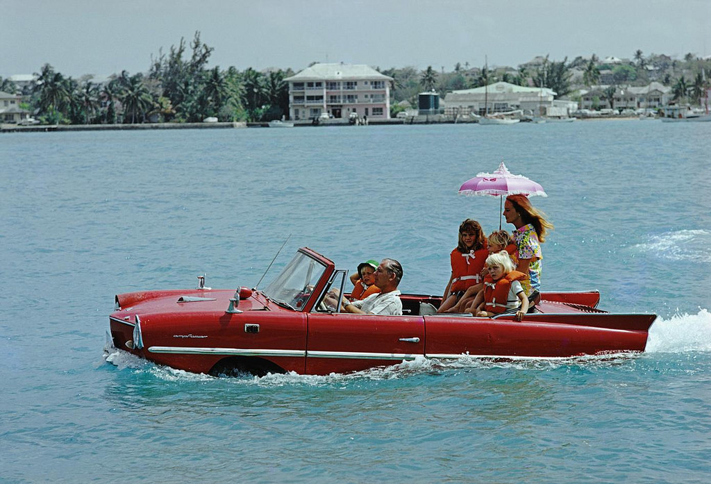 Slim Aarons captures film producer Kevin McClory takes his wife Bobo Sigrist and their family for a drive in an 'Amphicar' across the harbour between Paradise Island and Nassau, 1967. Hanging in  Cottage Sweet Escape .
