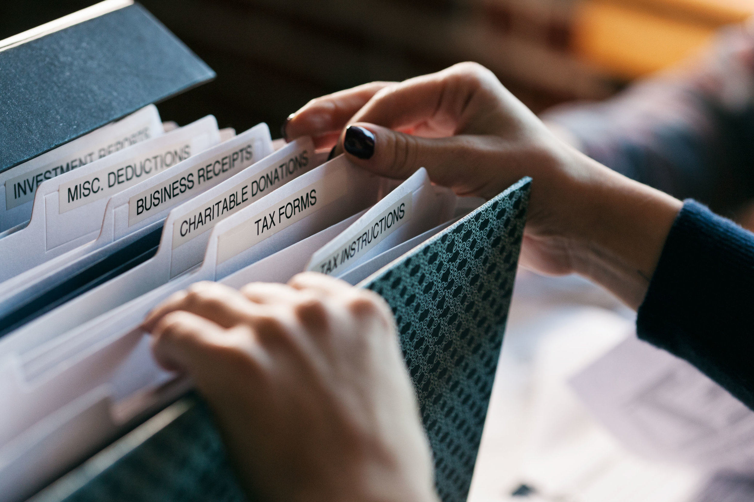 Taxes: Woman Digging Through Tax File Folder For Forms