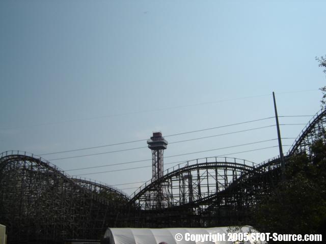Oil Derrick peaks over Texas Giant's wooden structure.
