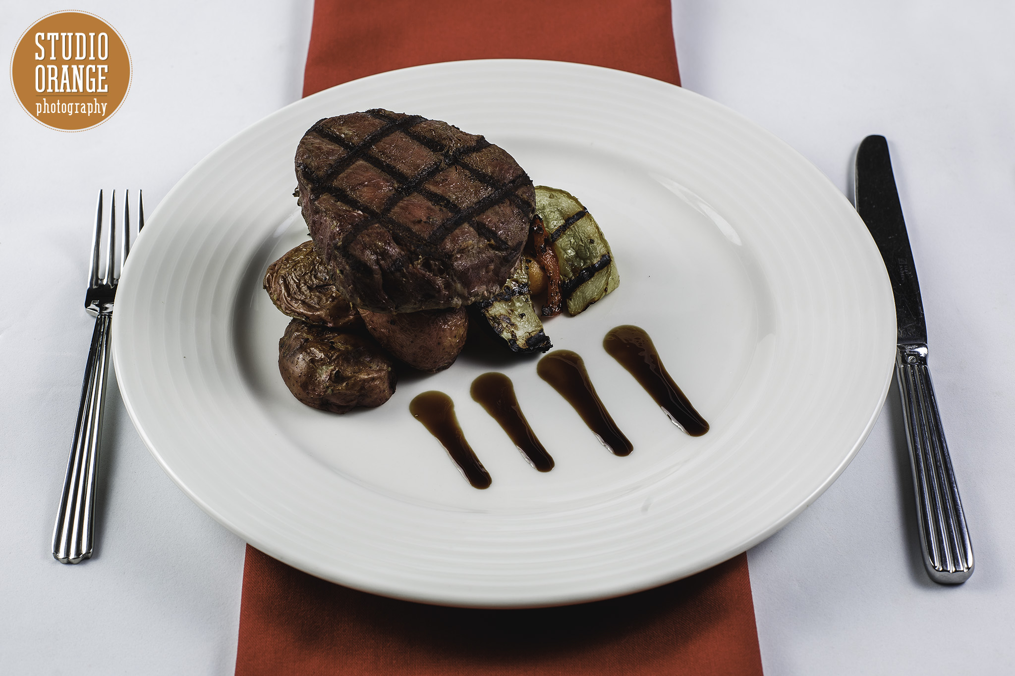 Steak Sirloin - Steak Tenderloin cooked to perfection (Medium) and glazed with a merlot wine reduction. Served on a bed of confit potatoes and grilled vegetable medley.(Gluten Free)
