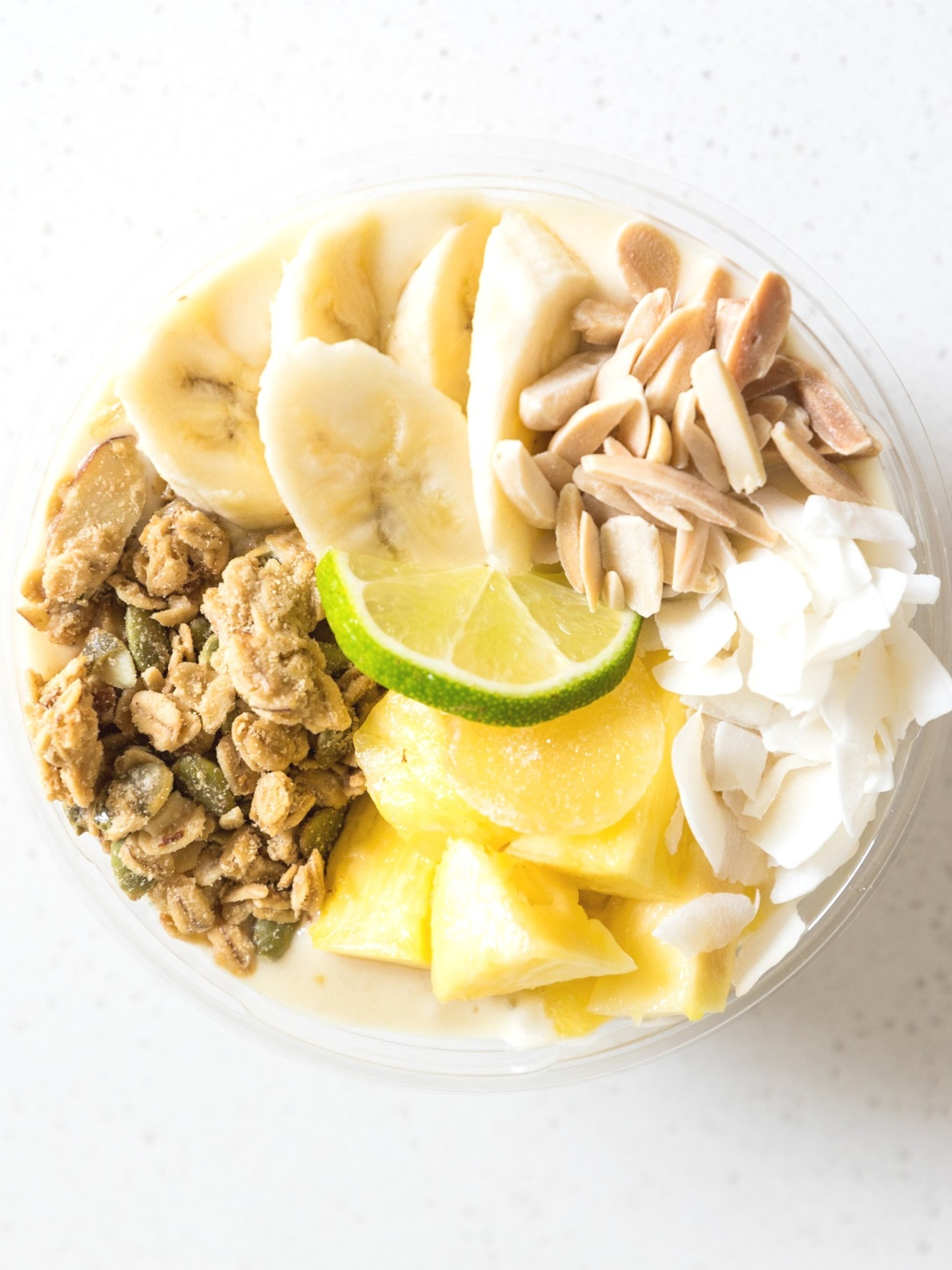 Cocolada : Pineapple / Banana / Coconut Milk / Lime  Topped with Granola, Sliced Almonds, Banana, Shredded Coconut, Lime Wedge, Candied Ginger