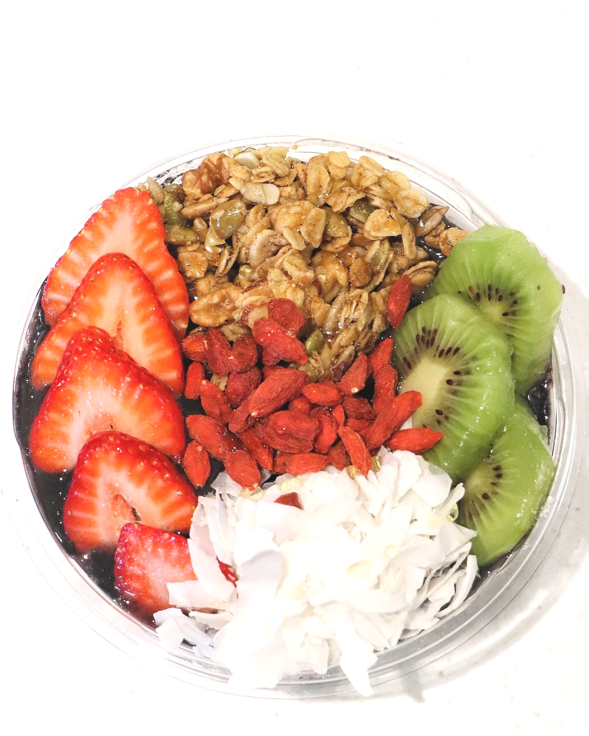 Black Majik:  Activated Charcoal / Blueberry / Strawberry / Banana / Coconut Water  Topped with Granola, Kiwi, Strawberries, Coconut, Goji Berries