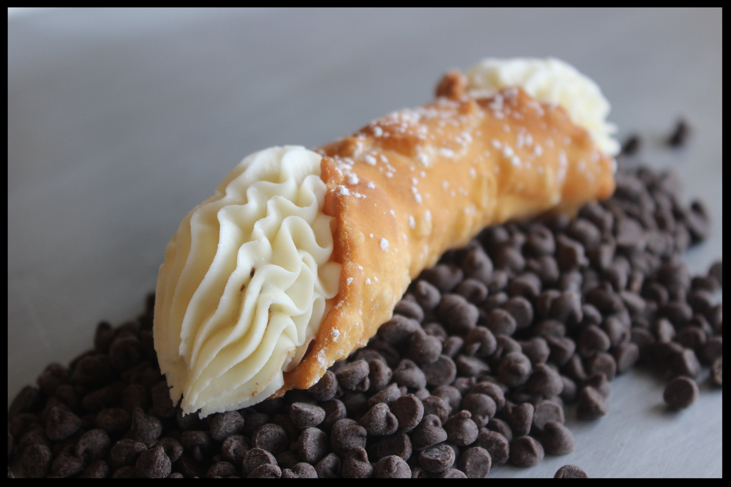 Cannoli - Fried Cannoli shell made in house with sweetened ricotta cheese and chocolate chips.