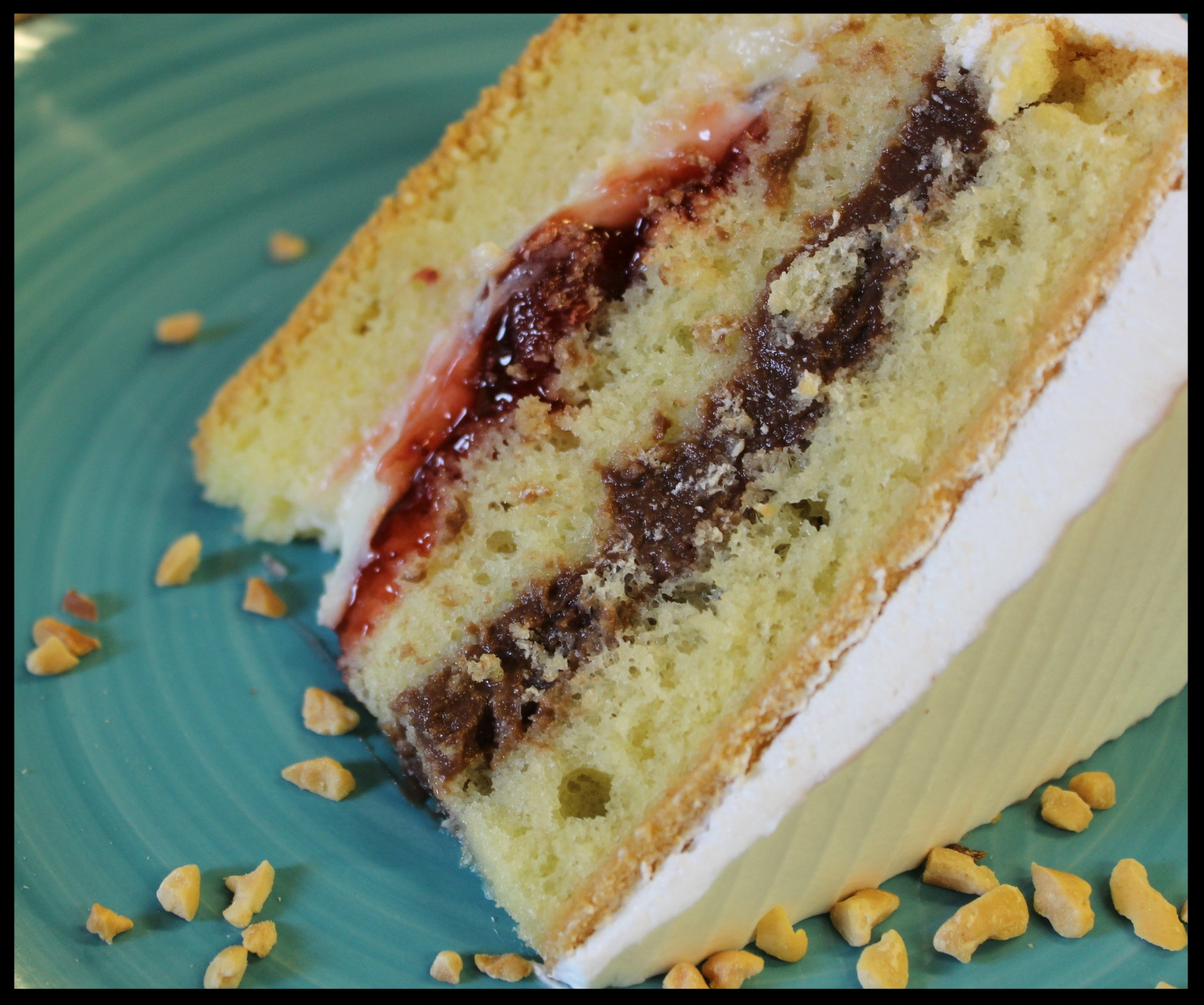 Rum Cake Slice - Rum flavored sponge with chocolate cream, mixed cream, strawberry, buttercream frosting and peanuts.