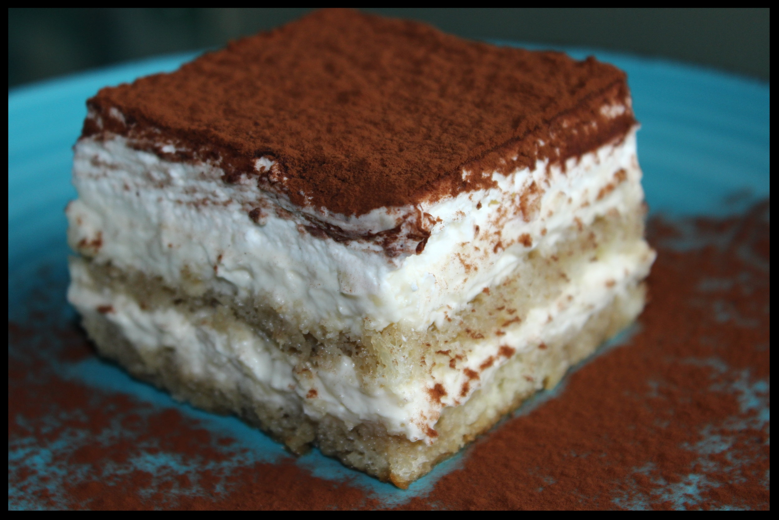 Tiramisu - Our tiramisu is sponge cake soaked in brandy and espresso, with a filling made with marsala wine, topped with whipped cream and cocoa.