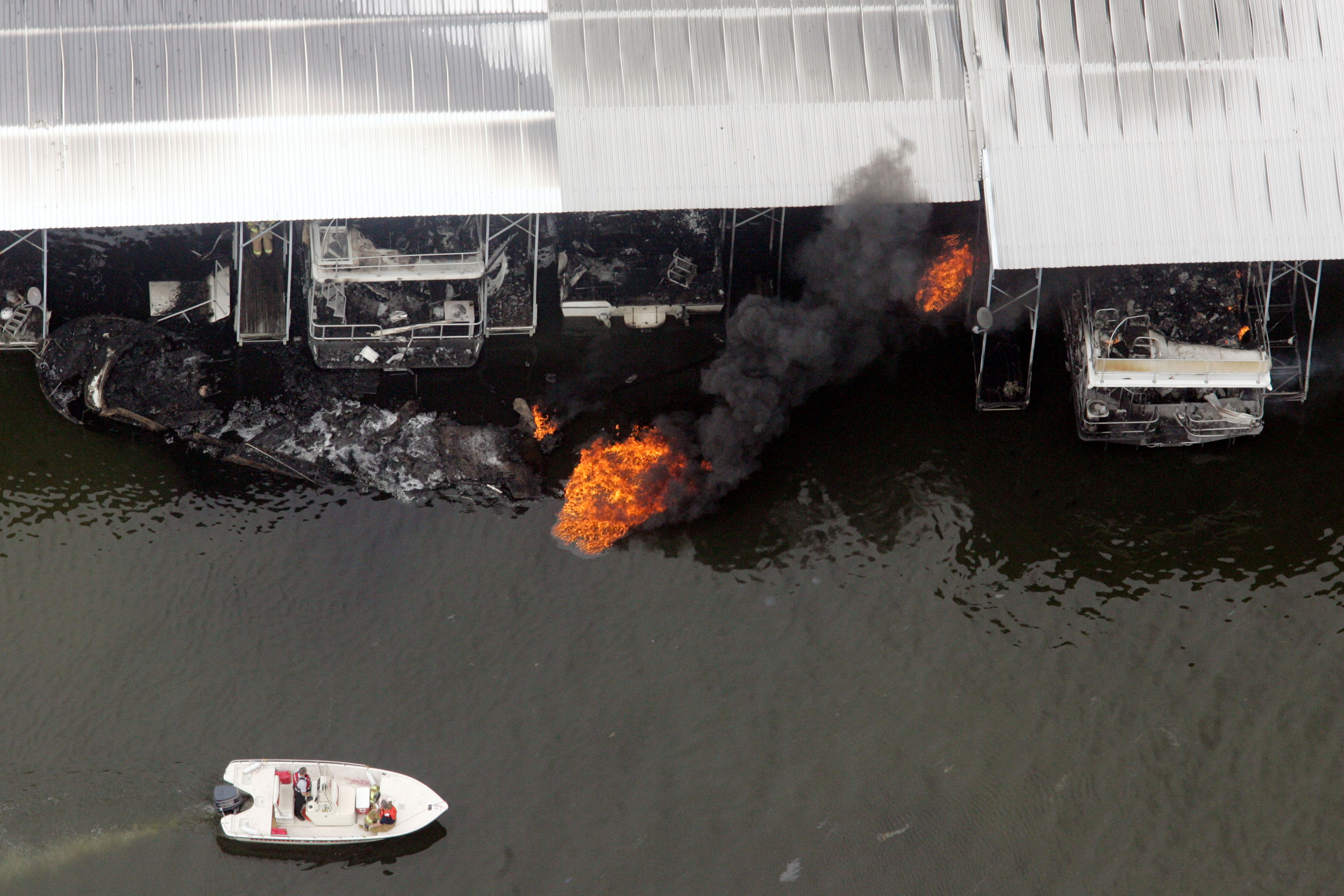 A boat motors by a fire that broke out in the marina March 8, 2006 in Hendersonville, Tenn.