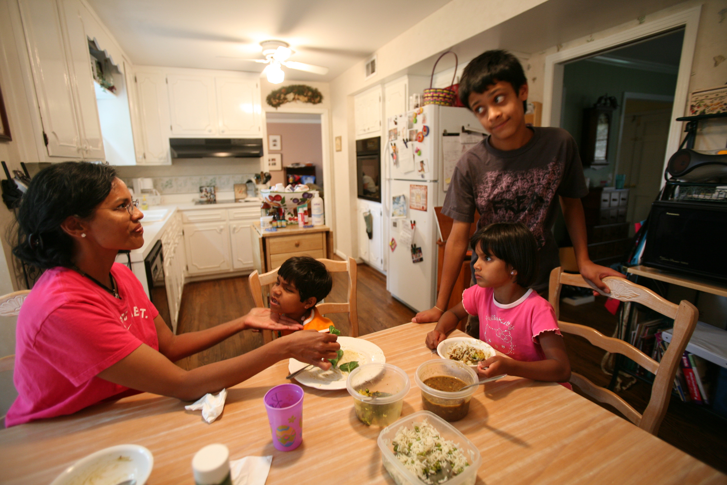 Karthi Masters, left, feeds Kajal at the dinner table with her children Davey, and Elijah in Franklin, Tenn., Wednesday, May 30, 2007. The Masters, who want to adopt Kajal, have already adopted Davey from India several years ago.