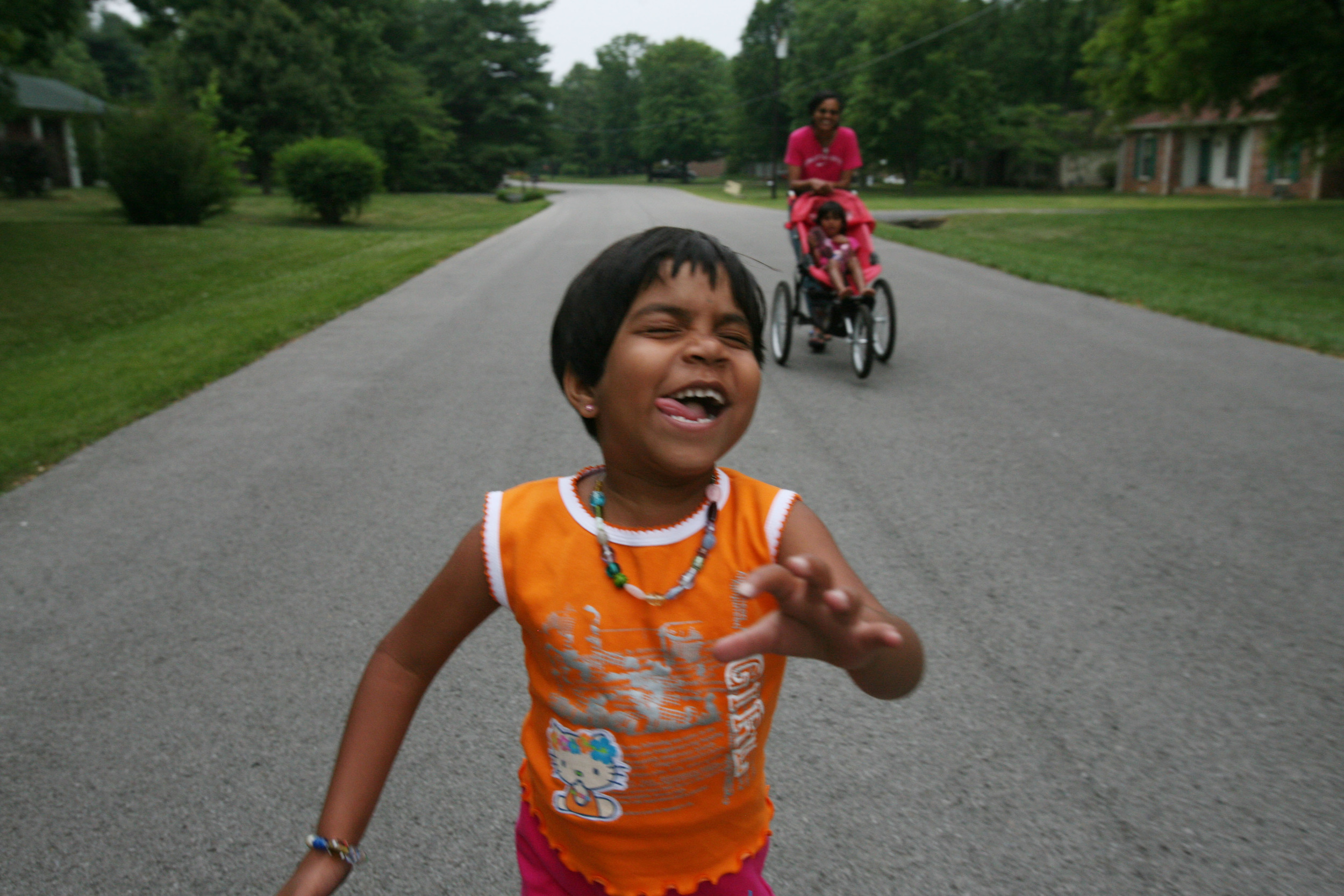 Kajal laughs as she runs down the middle of a quiet suburban street in Franklin, Tenn Wednesday, May 30, 2007. Despite the twists and turns of her difficult life, Kajal can be an exuberant and fearless child.