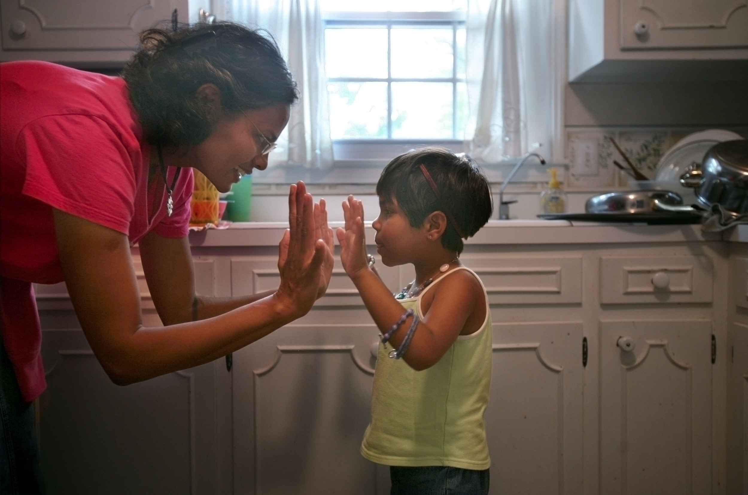 Karthi Masters gives Kajal a high five after she helped with the dishes Wednesday, May 30, 2007 in Franklin, Tenn. Kajal had developed a bond with Karthi and the Masters family.