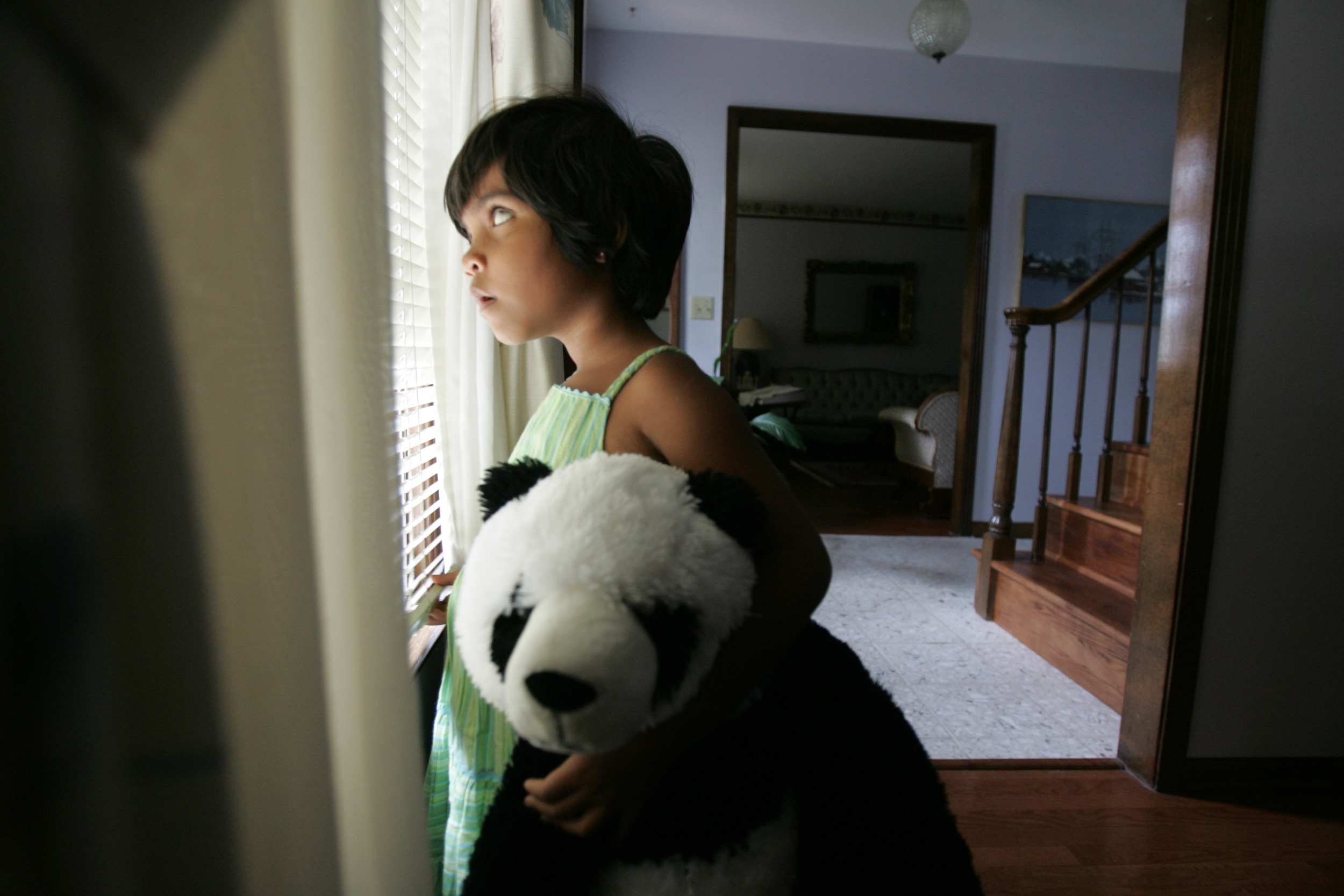 Kajal stands in front of a window at a second host family's house in Bellevue September 13, 2007. Her future uncertain, Kajal's journey in the U.S. has been fraught with complications and heartbreak.