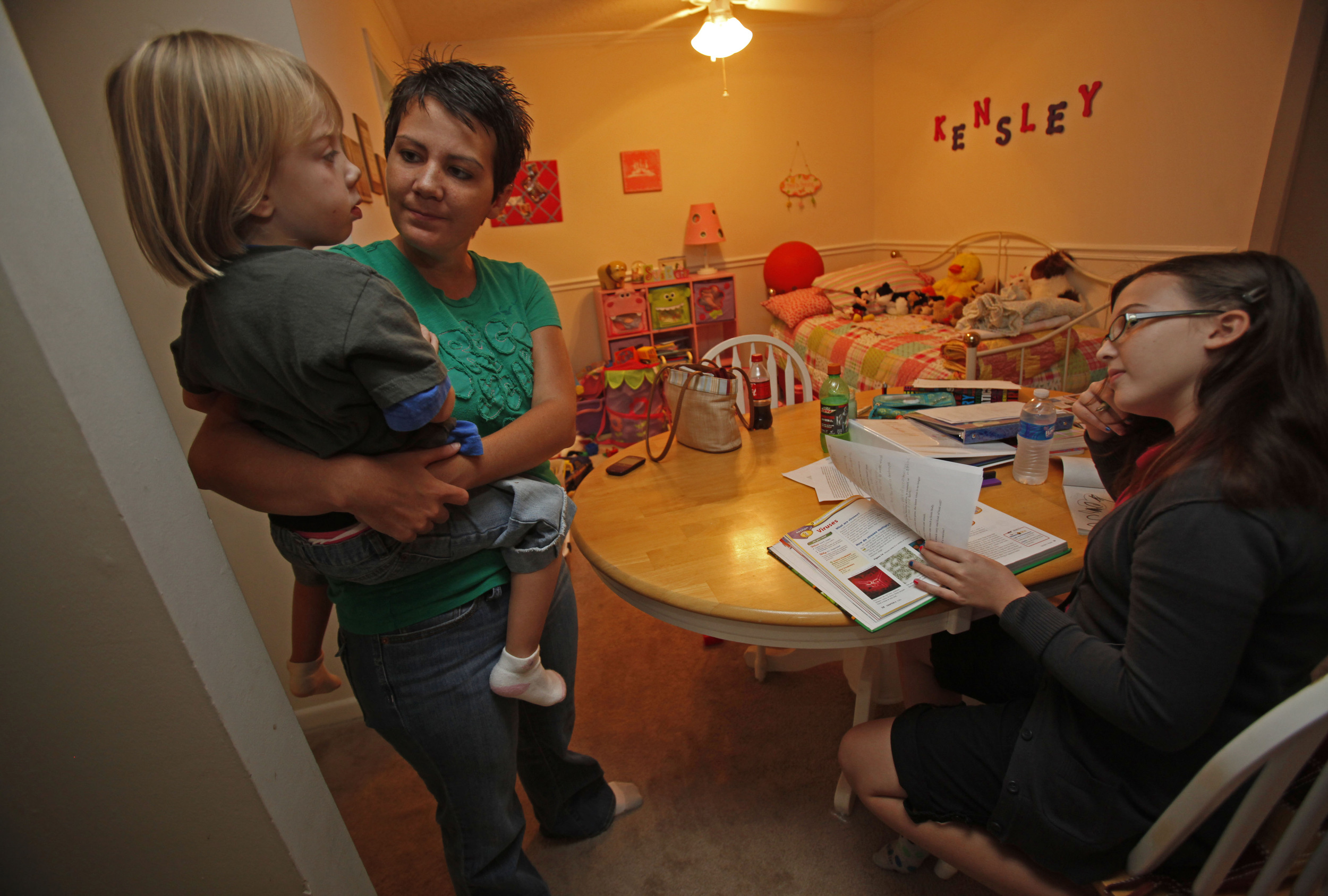 Lori Harrington and daughters Jasey, 12, and Kensley, 4, spend evenings around the kitchen table in their small apartment September 8, 2010 in Nashville, Tenn. Harrington moved to an apartment and left her job due to the stress of recovering from the flood.