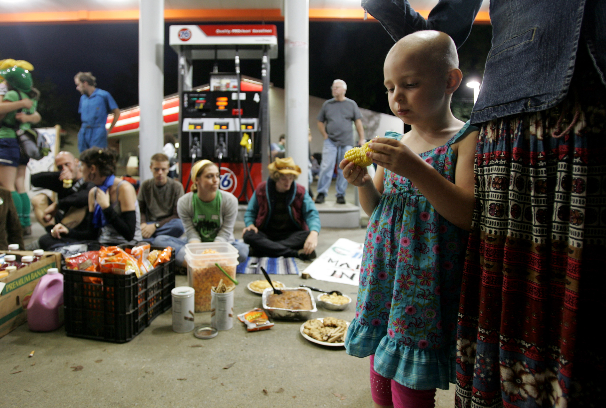 Nova Potter, 4, eats corn on the cob at a gas station where Food not Bombs had set up free food outside the town hall debate.