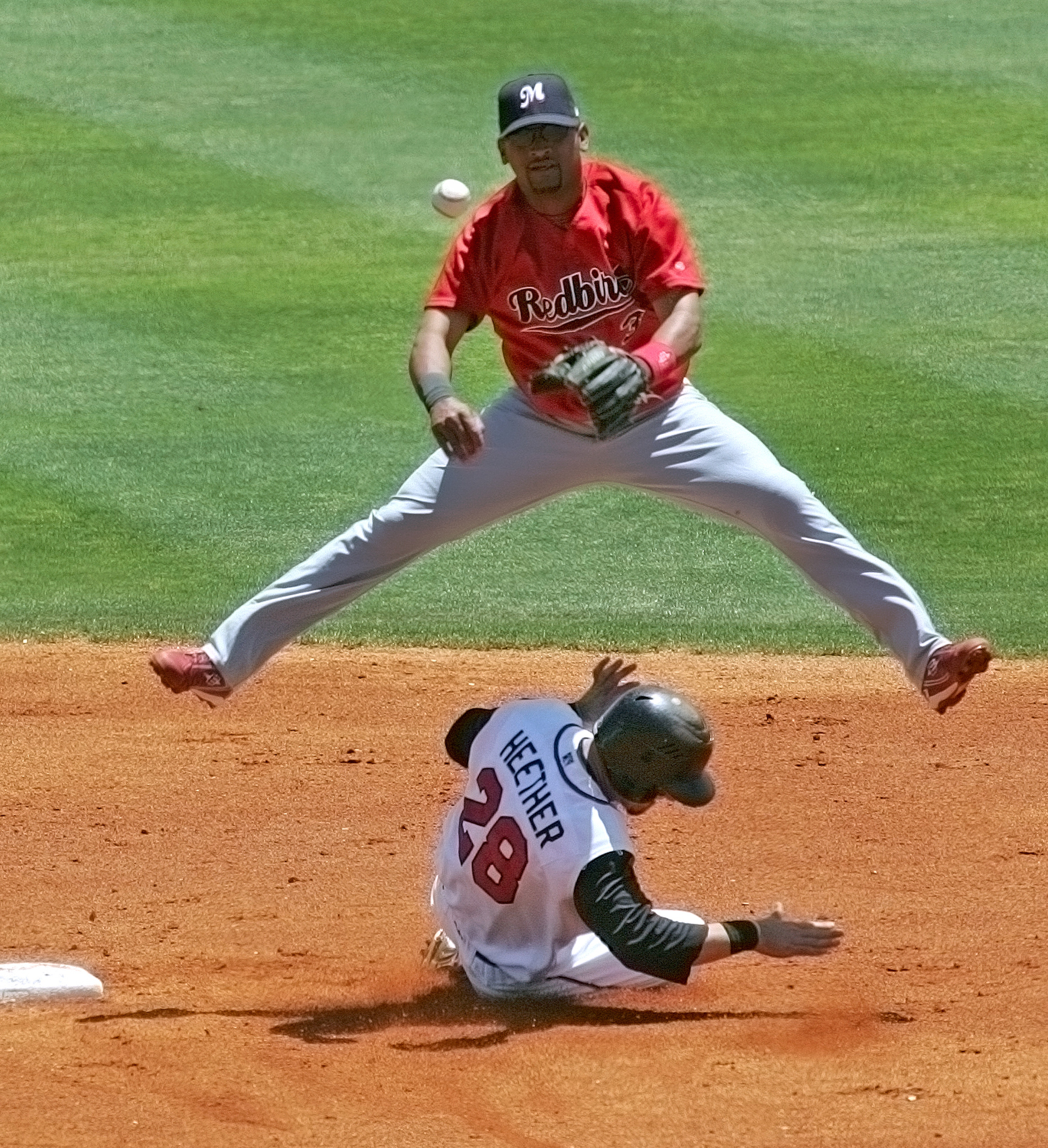 Memphis Redbirds shortstop D'Angelo Jiminez (3) throws to first for a double play and leaps over The Sounds' Adam Heether (28) as he slides into second May 21, 2008 in Nashville, Tenn.