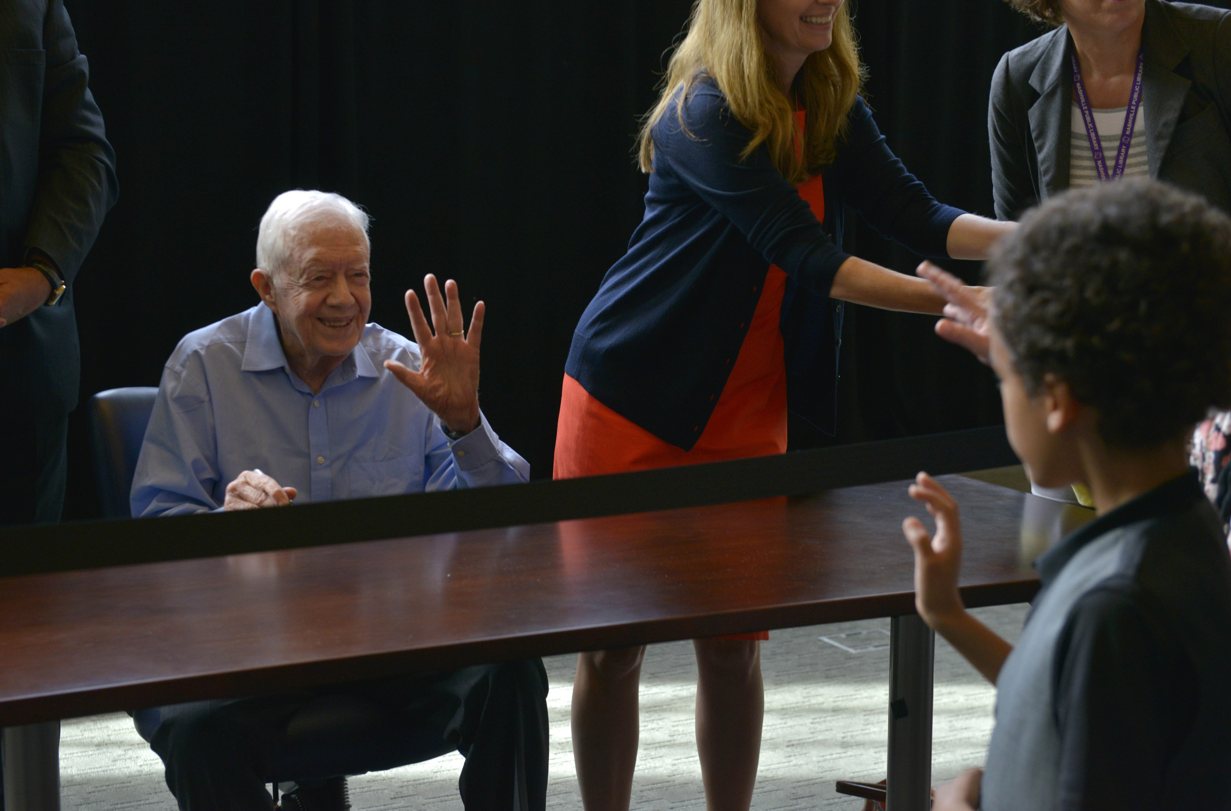 Former President Jimmy Carter waves to a young boy as he does a book signing at the downtown branch of the Nashville Public Library July 23, 2015 in Nashville, Tenn.