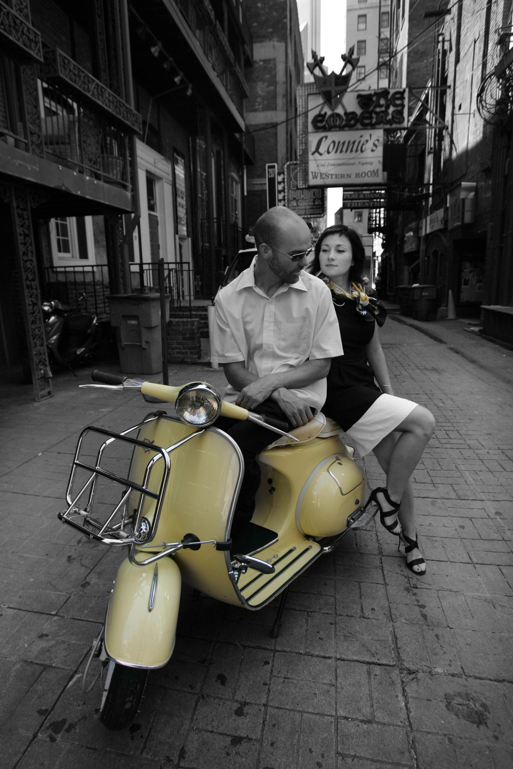 Keith Harmon with Brooke Cawthon on his Vespa yellow 1966 Sears Allstate in Printers Alley in Nashville, Tenn.