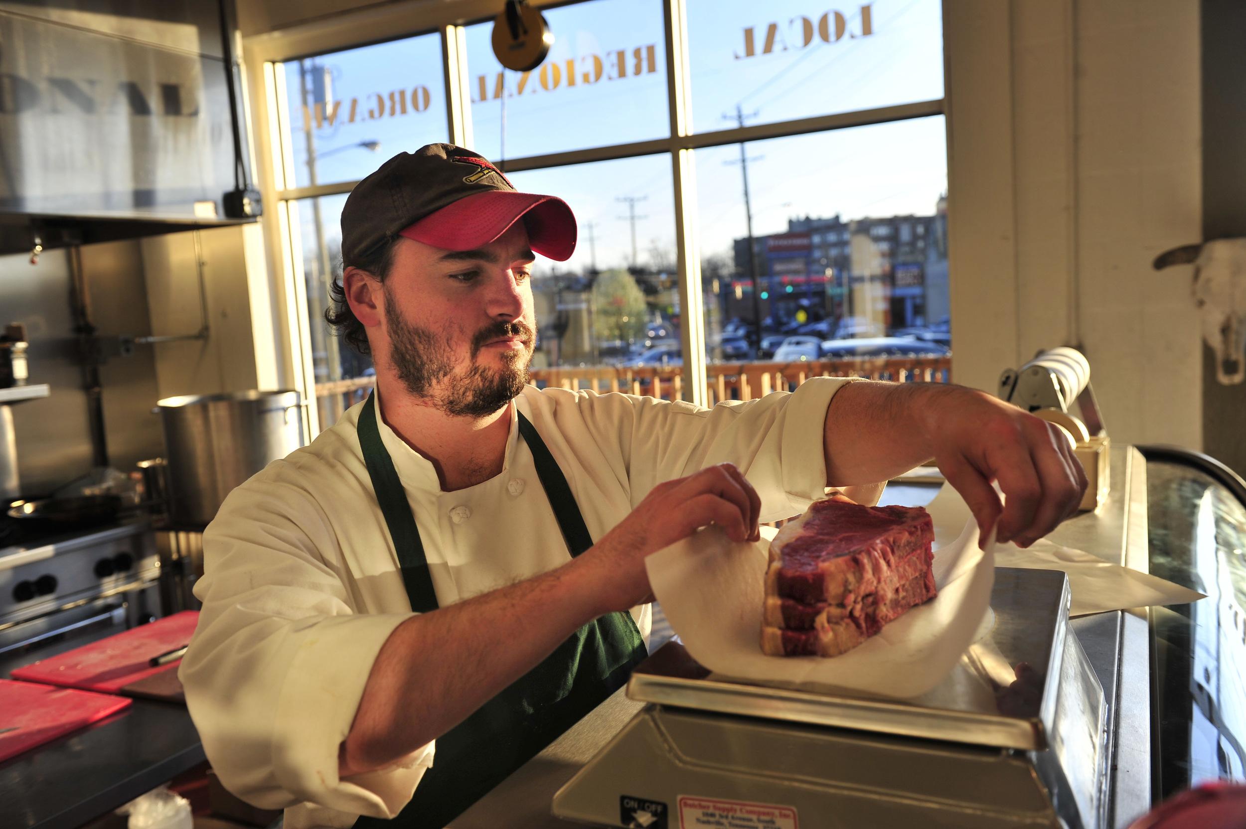 Co-founder James Peisker weighs freshly cut steaks at Porter Road Butcher in Nashville, Tenn.