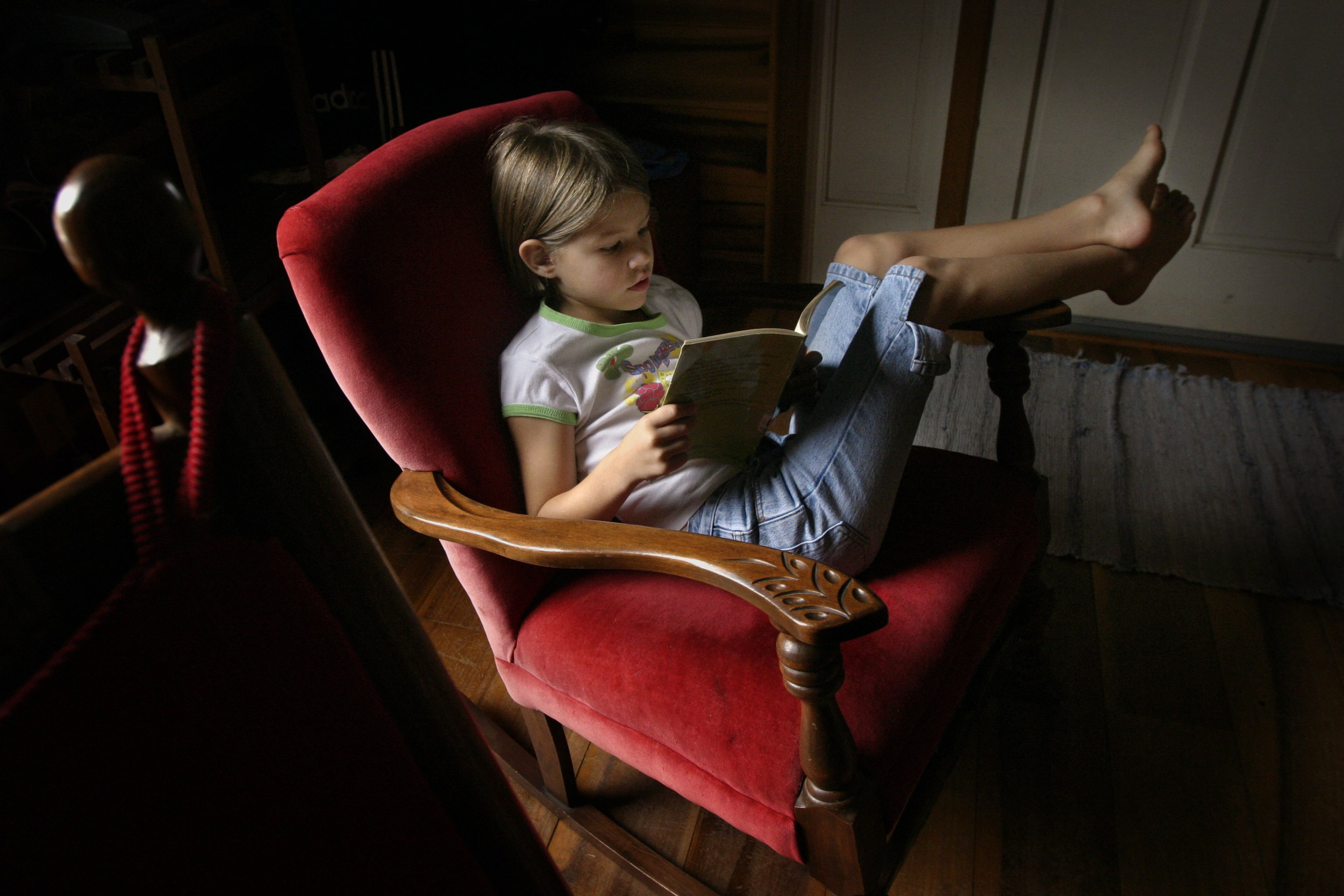 Anna Stewart Burdette, 7, lounges in a comfortable chair near the window during reading time, a part of her homeschool day.