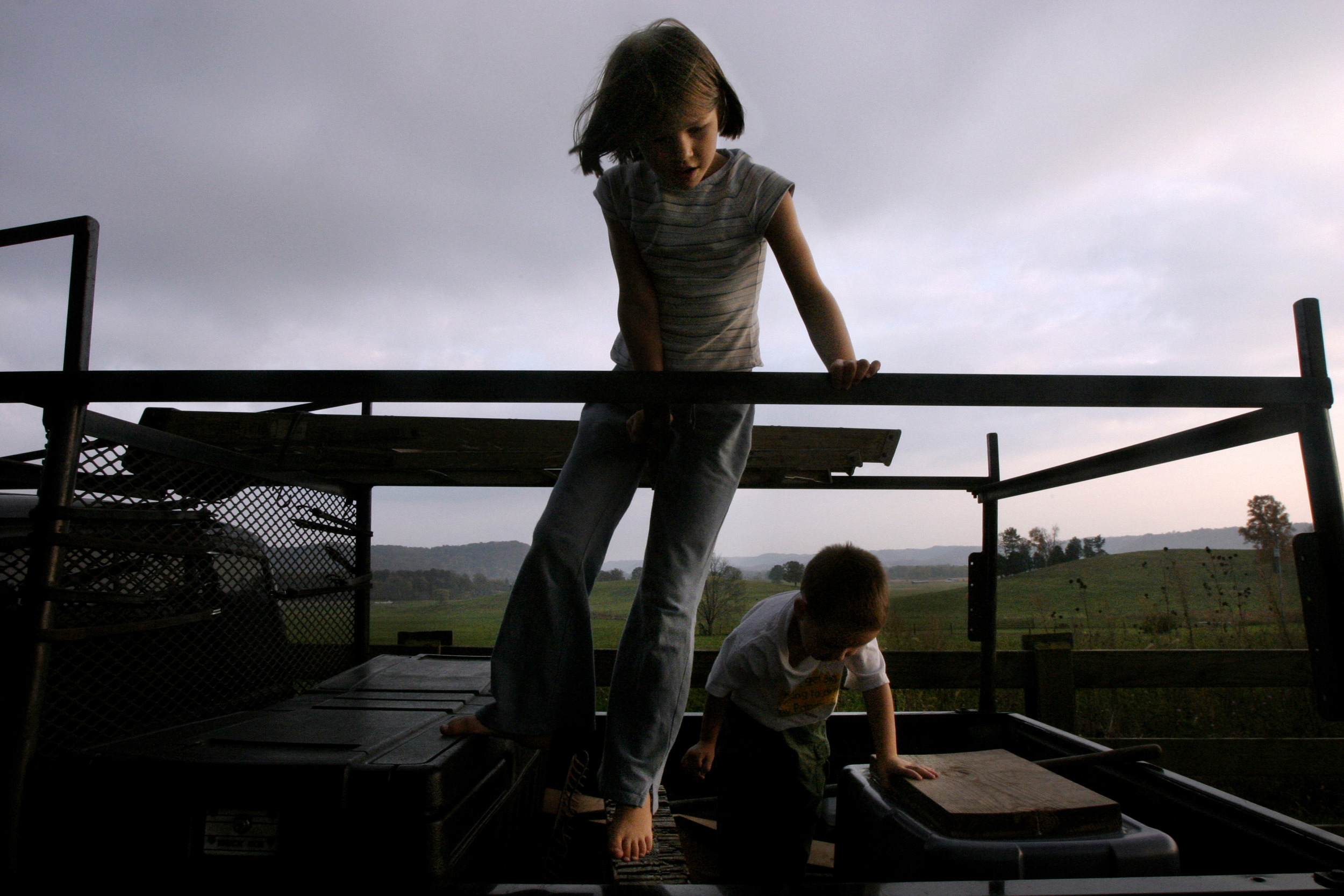 Anna Stewart Burdette, 7, and Tibor, 4 play together on a pickup truck as the sun sets over the vista of rolling hills and fields behind their house.