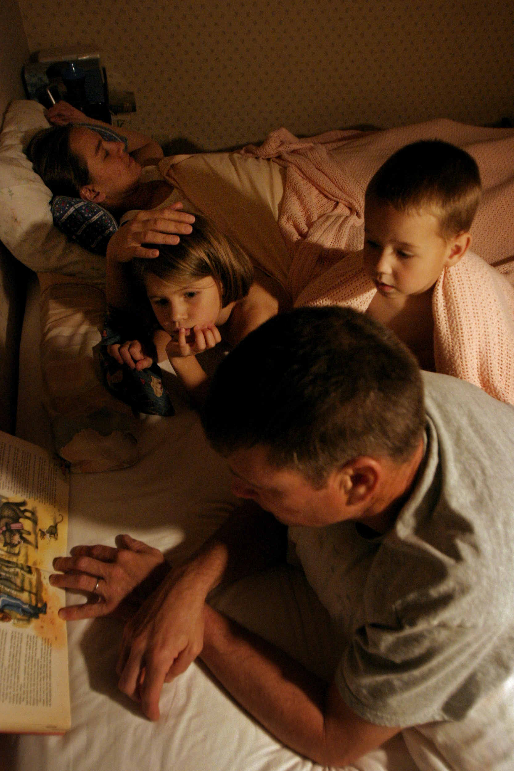 Pat Burdette reads to the children at bedtime as they fall asleep together.