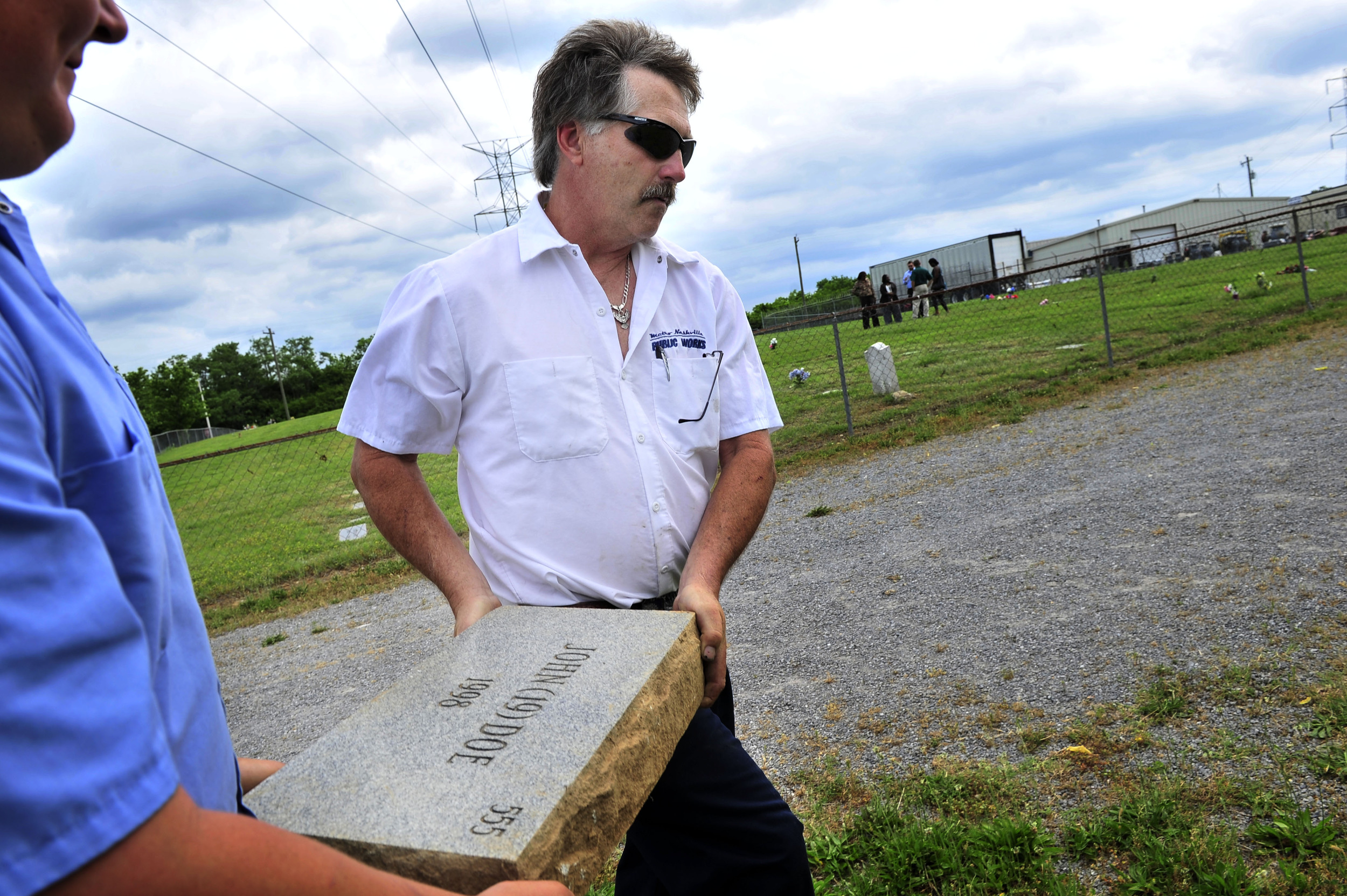 Danny Hubble, right, with Metro Public Works carries the John Doe gravestone away after replacing it with LeRyan Nicholson's named gravestone at Bordeaux Cemetary May 30, 2013 in Nashville, Tenn.