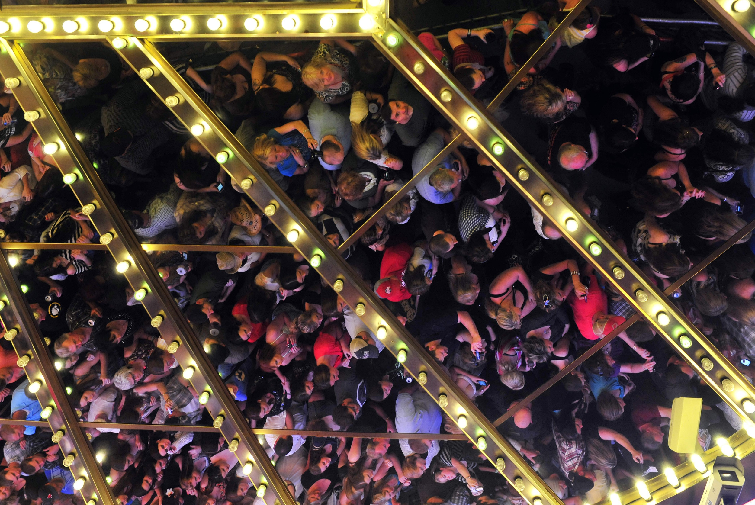 Fans reflected in a casino mirrored overhang are packed shoulder to shoulder at an outdoor concert in downtown Las Vegas during ACM week March 30, 2012 in Las Vegas, Nev.