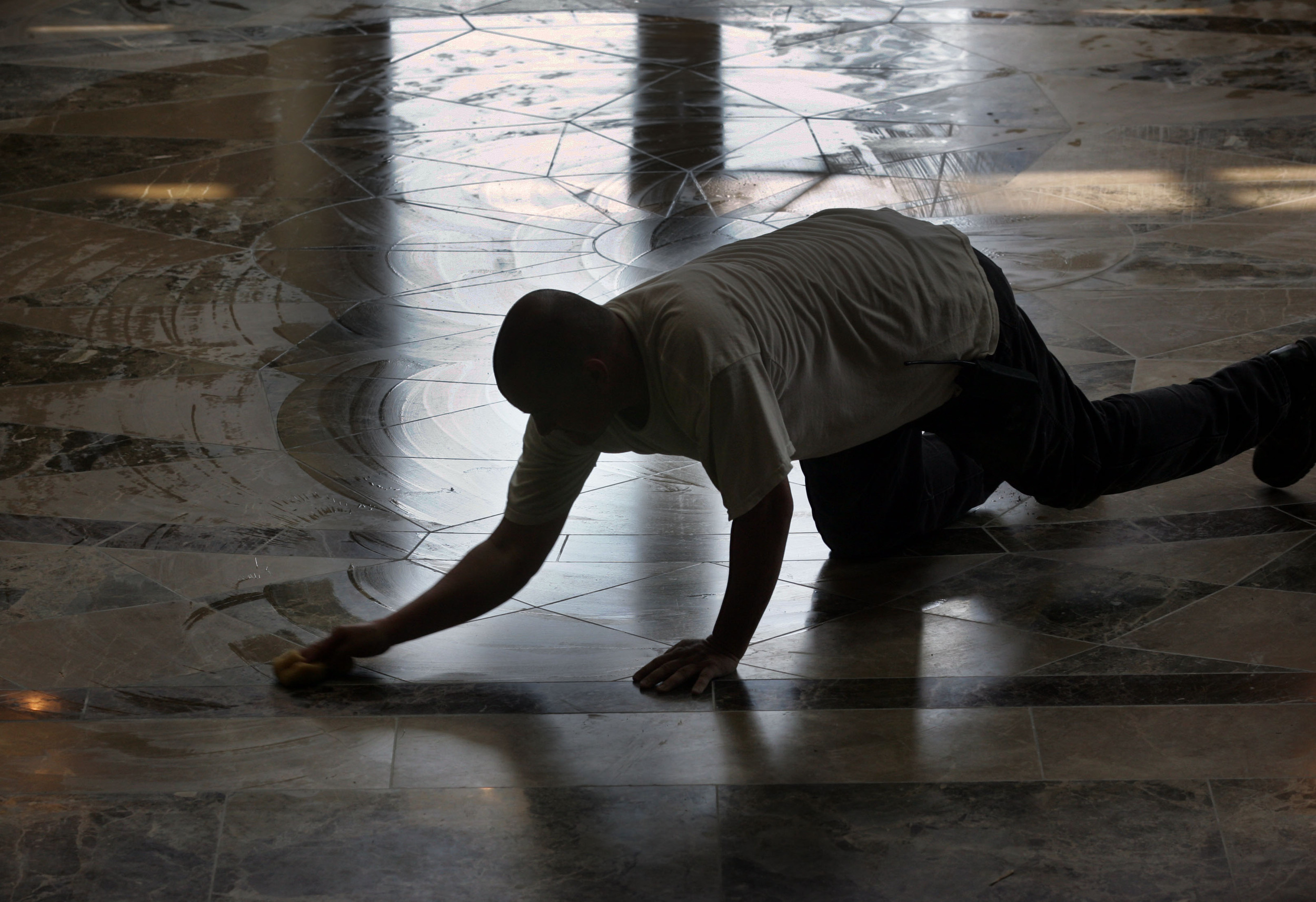 A worker wipes down the entrance floor, made from Spanish marble cut in Italy. The design is based on Michelangelo's design at the Piazza del Campidoglio.