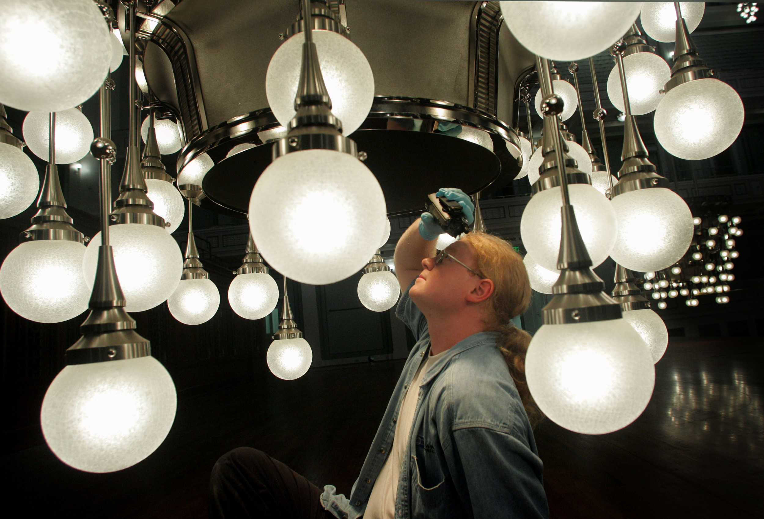 The neoclassical Schermerhorn Symphony Center opened in 2006 and was built over 3 years, employing thousands of specialized contractors and artisans.  Electrician Bobby Hopwood looks into a giant chandelier that hangs over the stage.