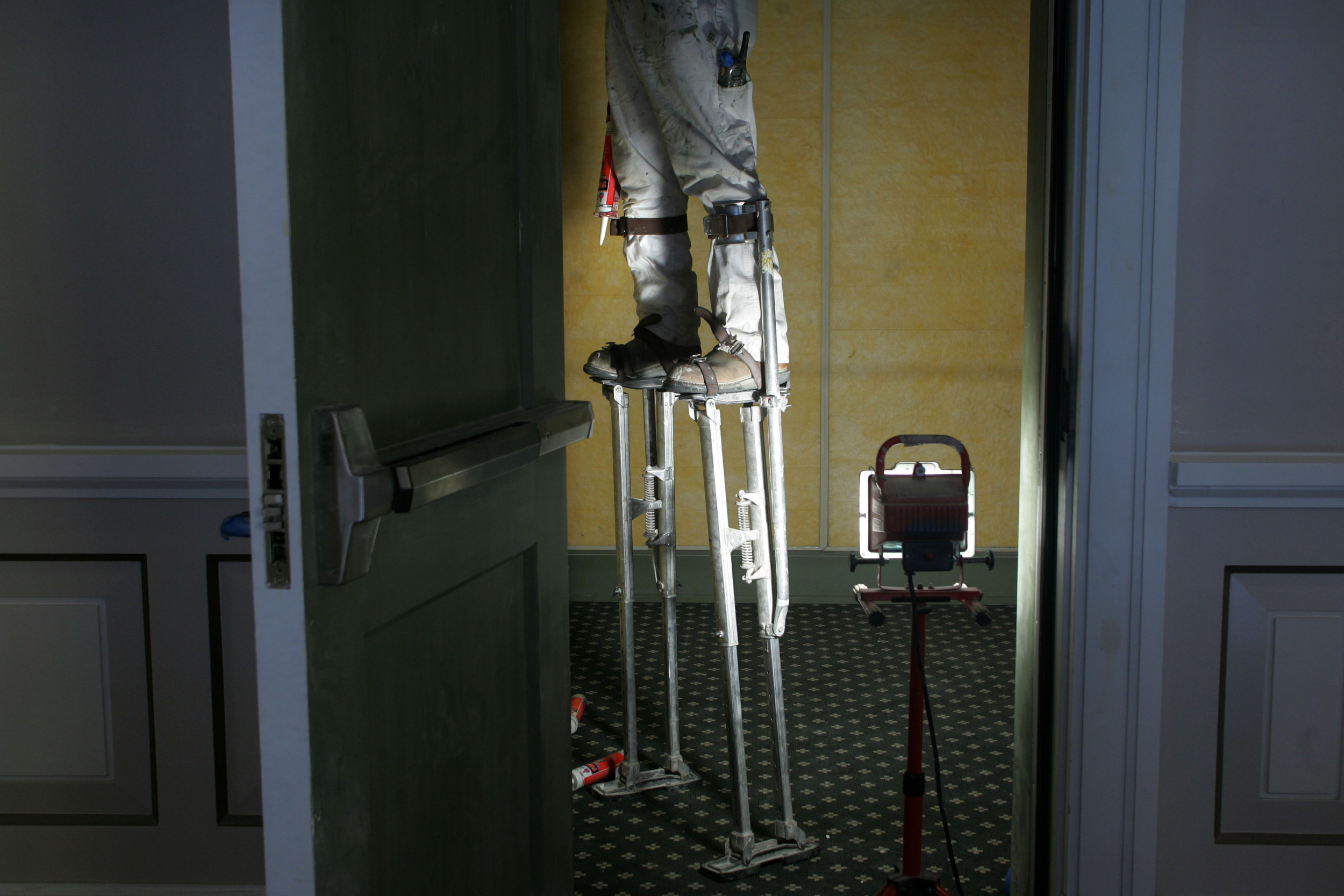 Hector Trujano with Bradley Coatings uses stilts to paint an interior room.