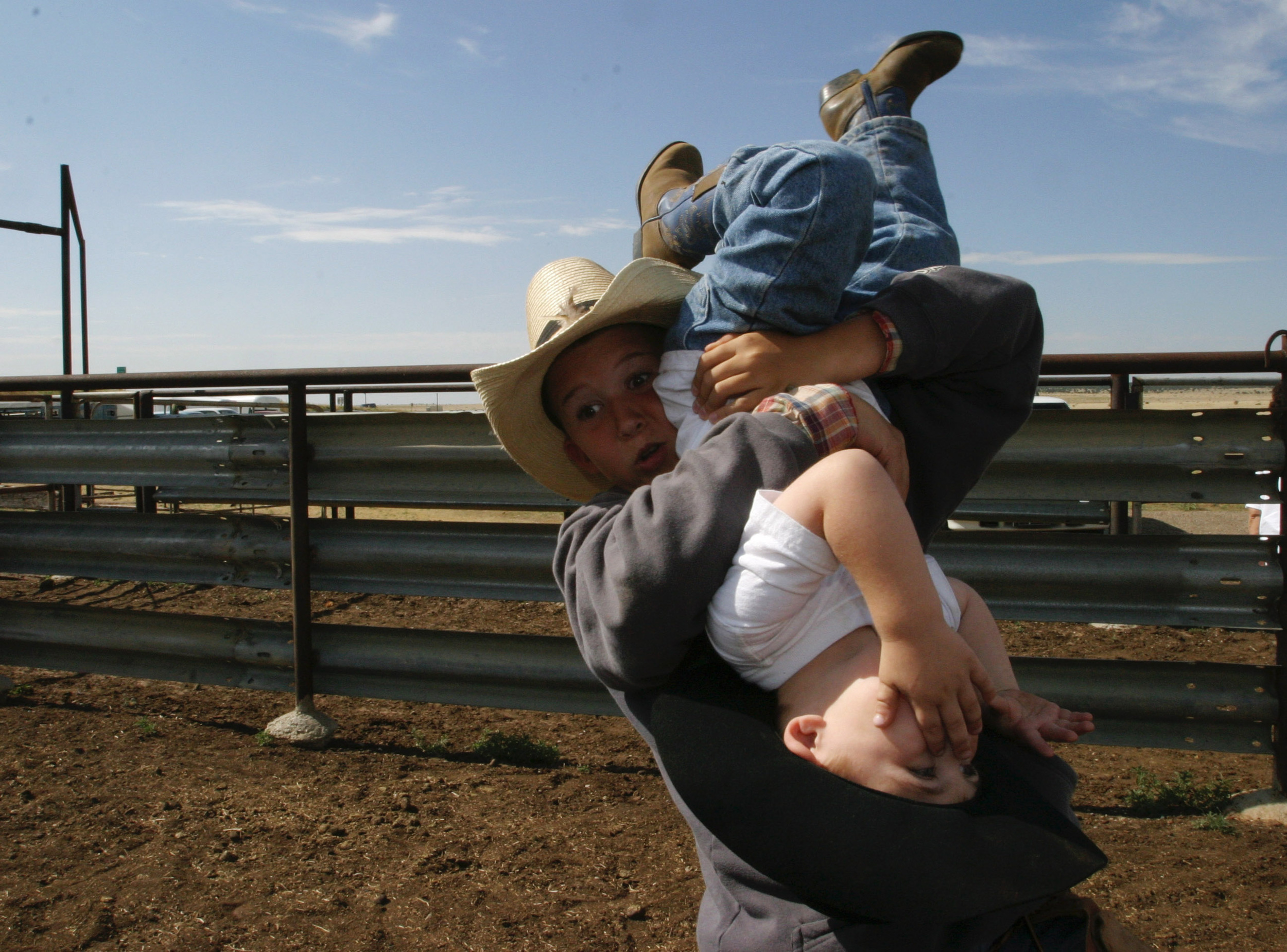 Truitt Frost, makes a face as he struggles to hold onto Andrew Martin Cribbs, 3, on the family ranch in New Mexico during a roundup.