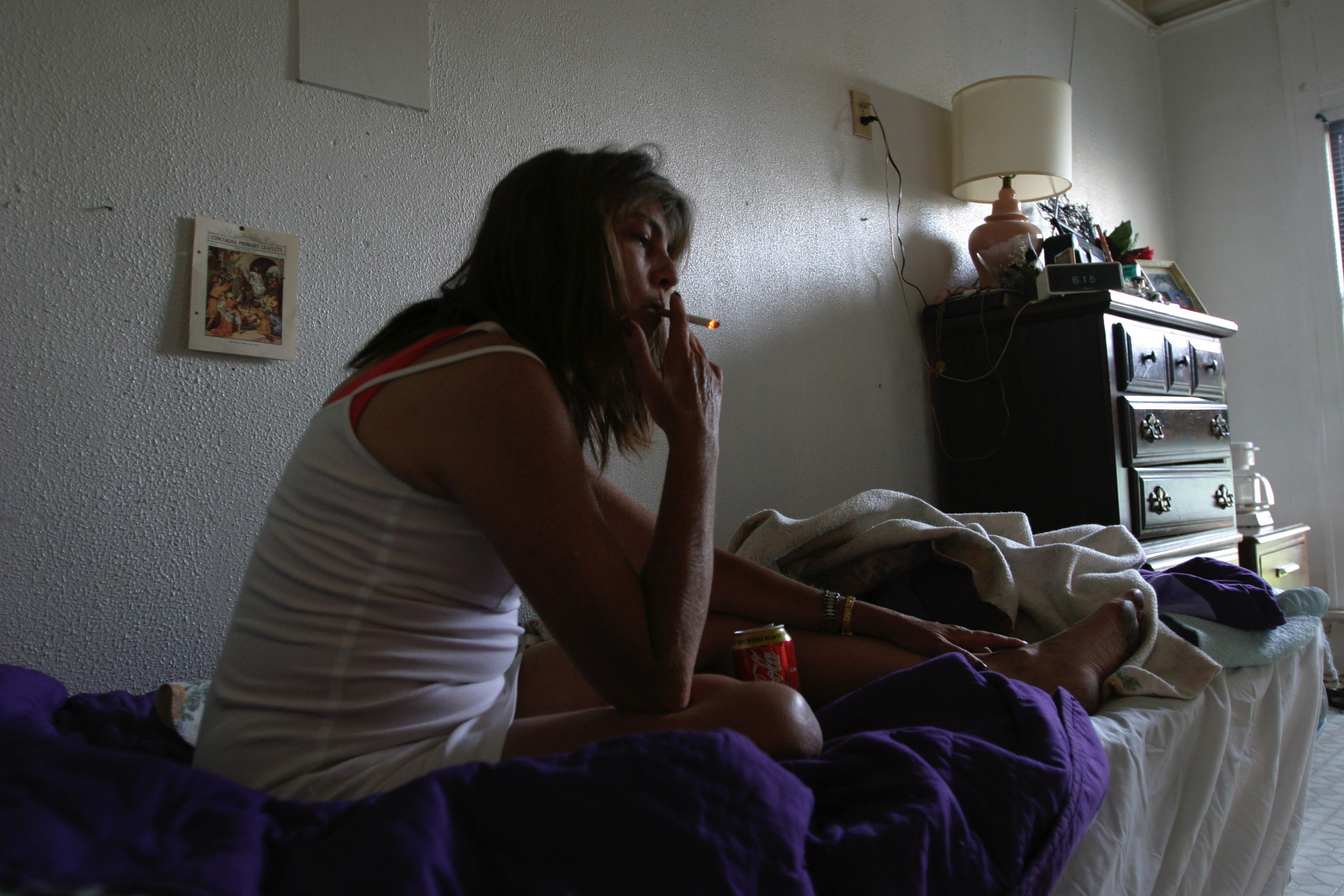 Cynthia has a smoke on her bed at the Drake guesthouse, formerly an upscale hotel in Carthage, Missouri along Route 66, now a group home for mentally and physically disabled.