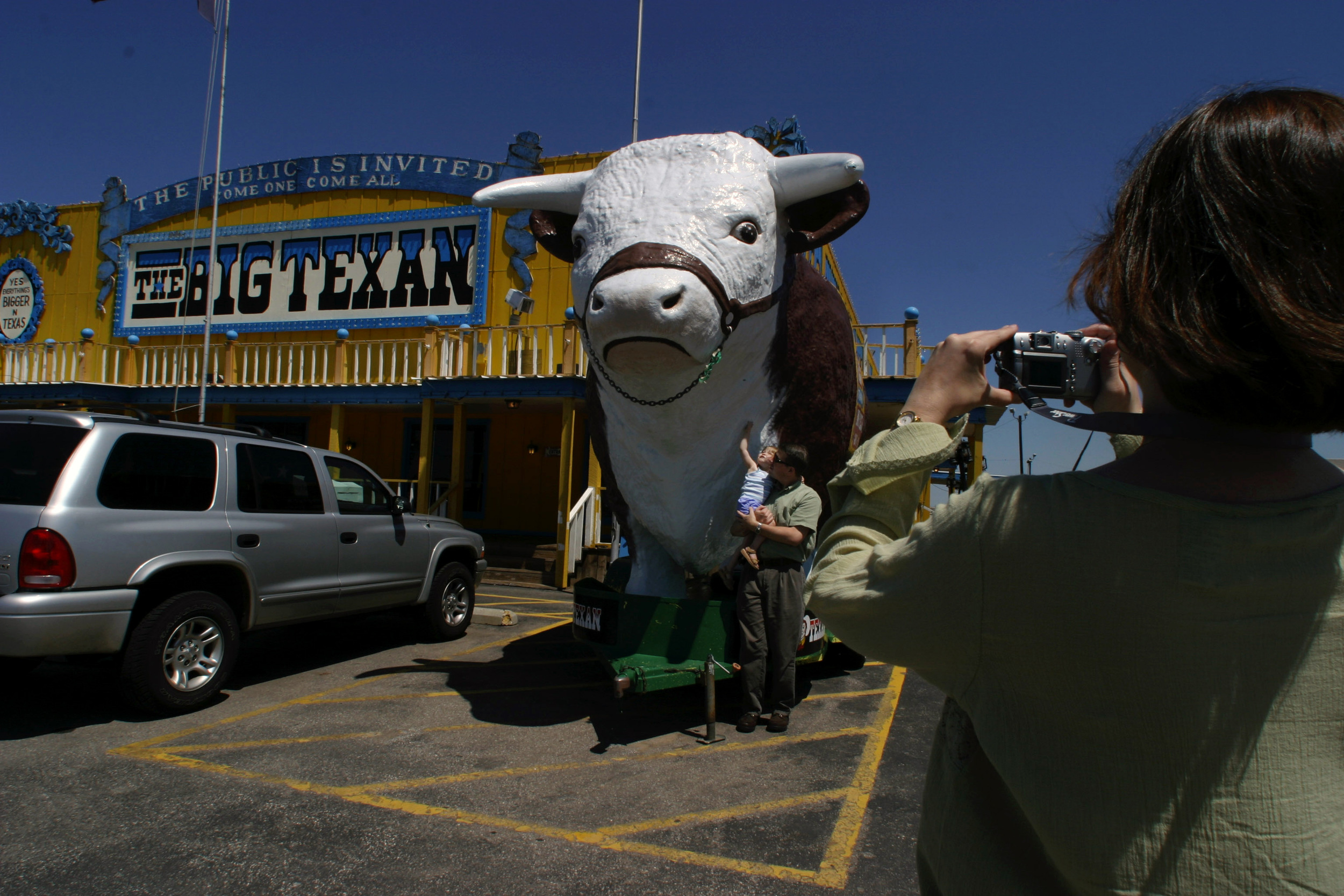 Tourists stop in at the Big Texan steakhouse to snap a photo with the giant cow in Amarillo, Texas.