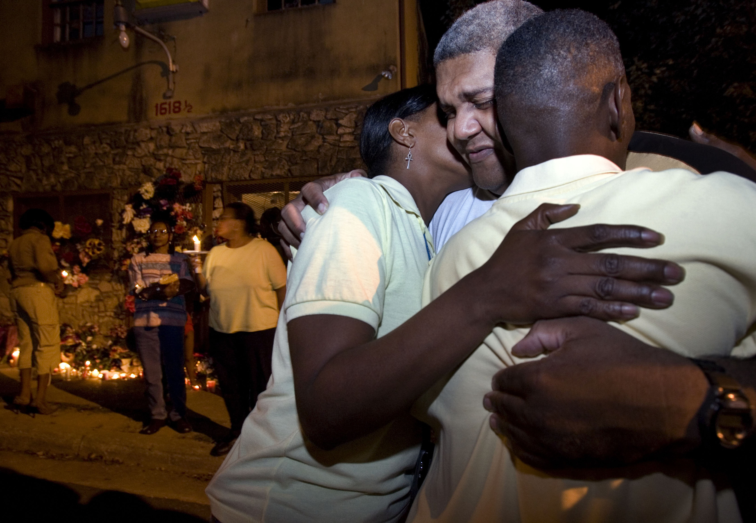 Ronald Wilson gets a hug in front of Cahal Market during a candlelight vigil for his mother Tuesday, October 9, 2007 in Nashville, Tenn. Classy Wilson, 70, a well-loved local and clerk at the market, was shot and killed by a middle schooler.