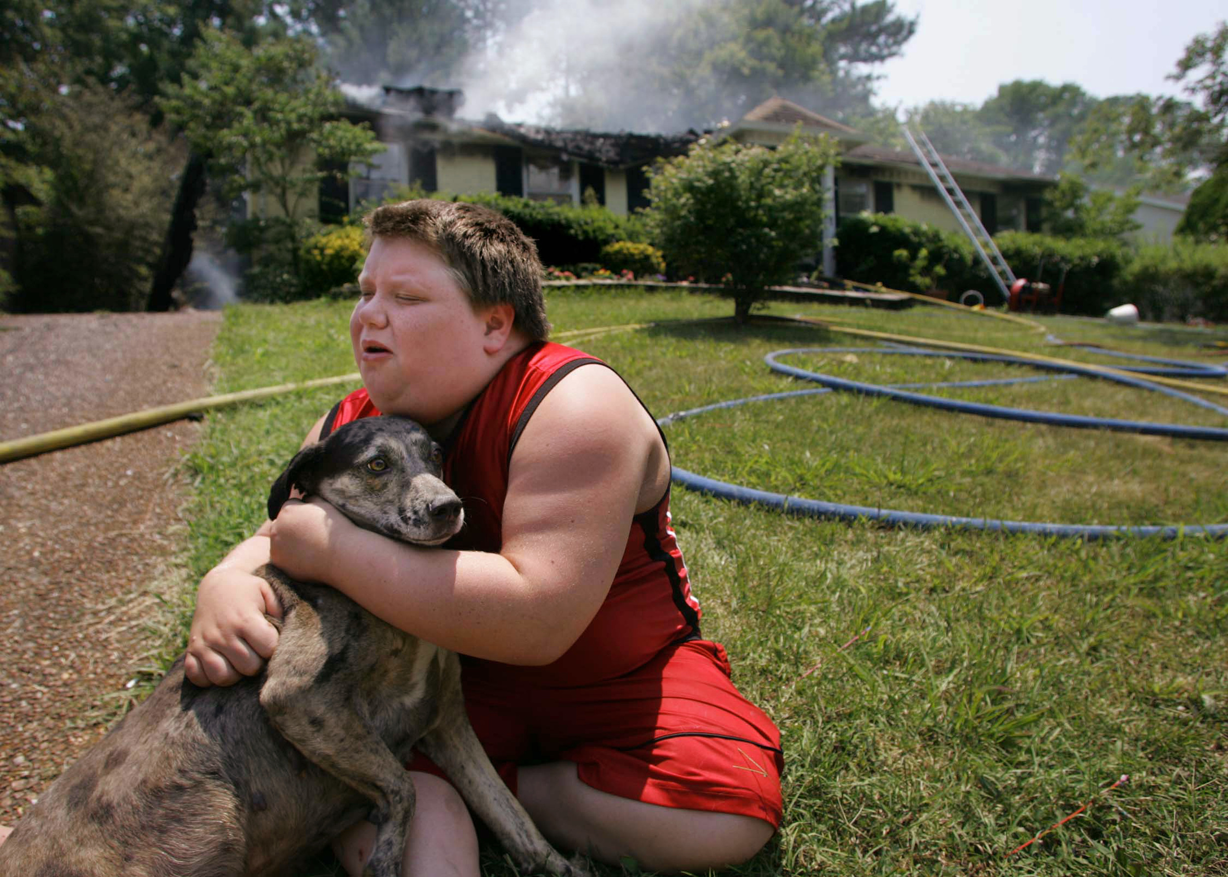 "Joseph Cunningham , 11, hugs his dog ""Vicious"" outside his grandmother's still-smoking house. He believed the dog had been trapped inside the fire but was found by a neighbor Friday, July 7, 2006 in Antioch, Tenn."