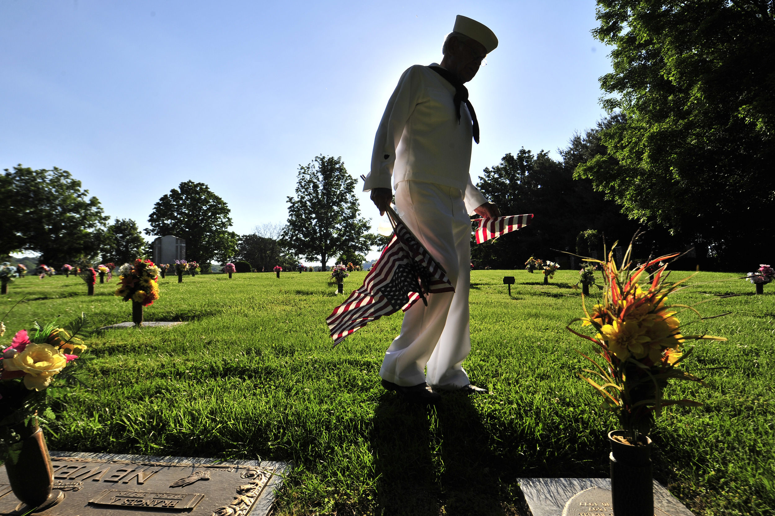 Coast Guard veteran Marty Gencsi plants flags on the graves of veterans at Williamson Memorial Garden Friday, May 24, 2013 in Franklin, Tenn.