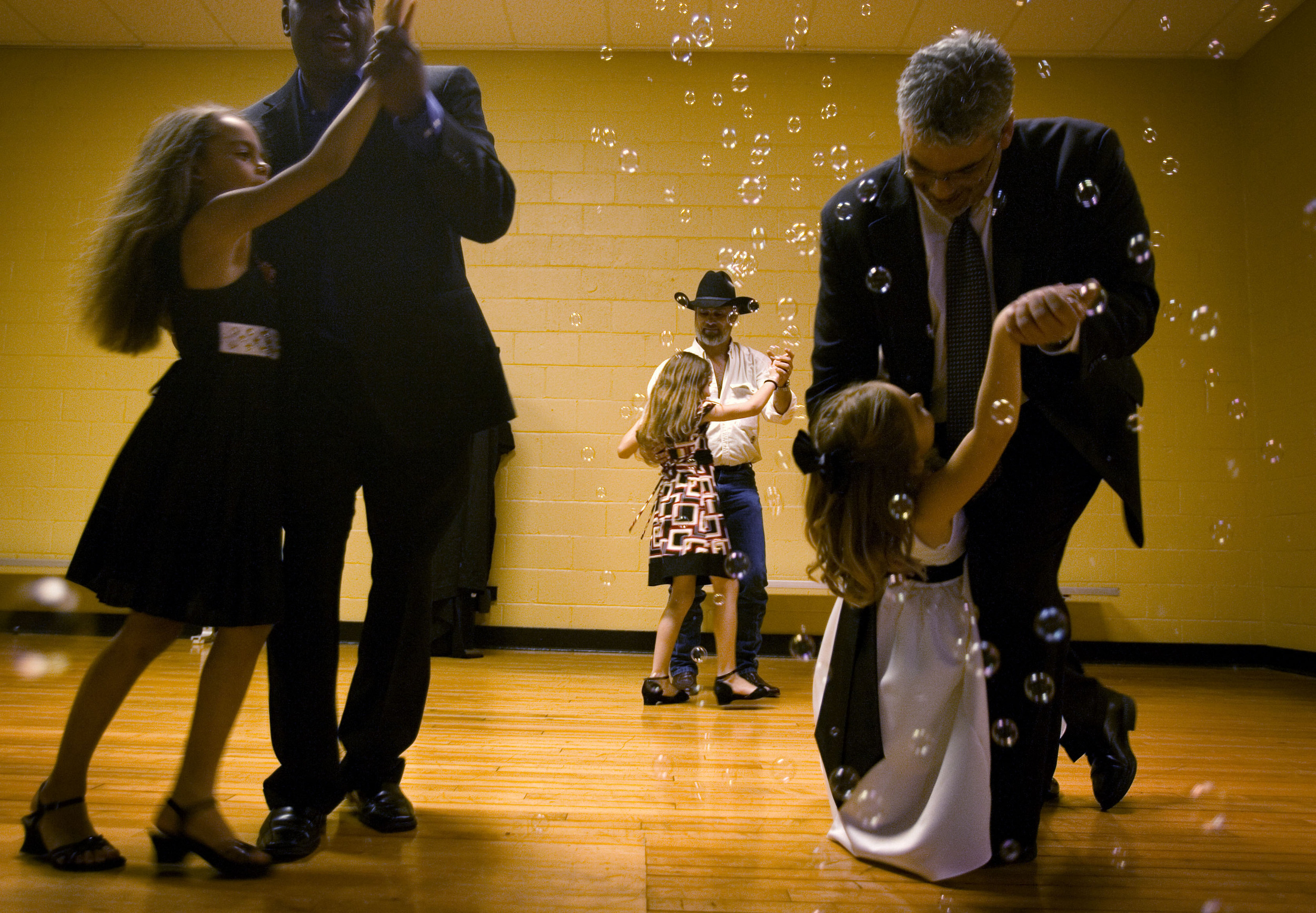 Father Roddy Ramirez, dips daughter Allison, 7, right, as they take the stage as one of the winners of the chicken dance contest during a father-daughter dance in Fairview, Tenn.