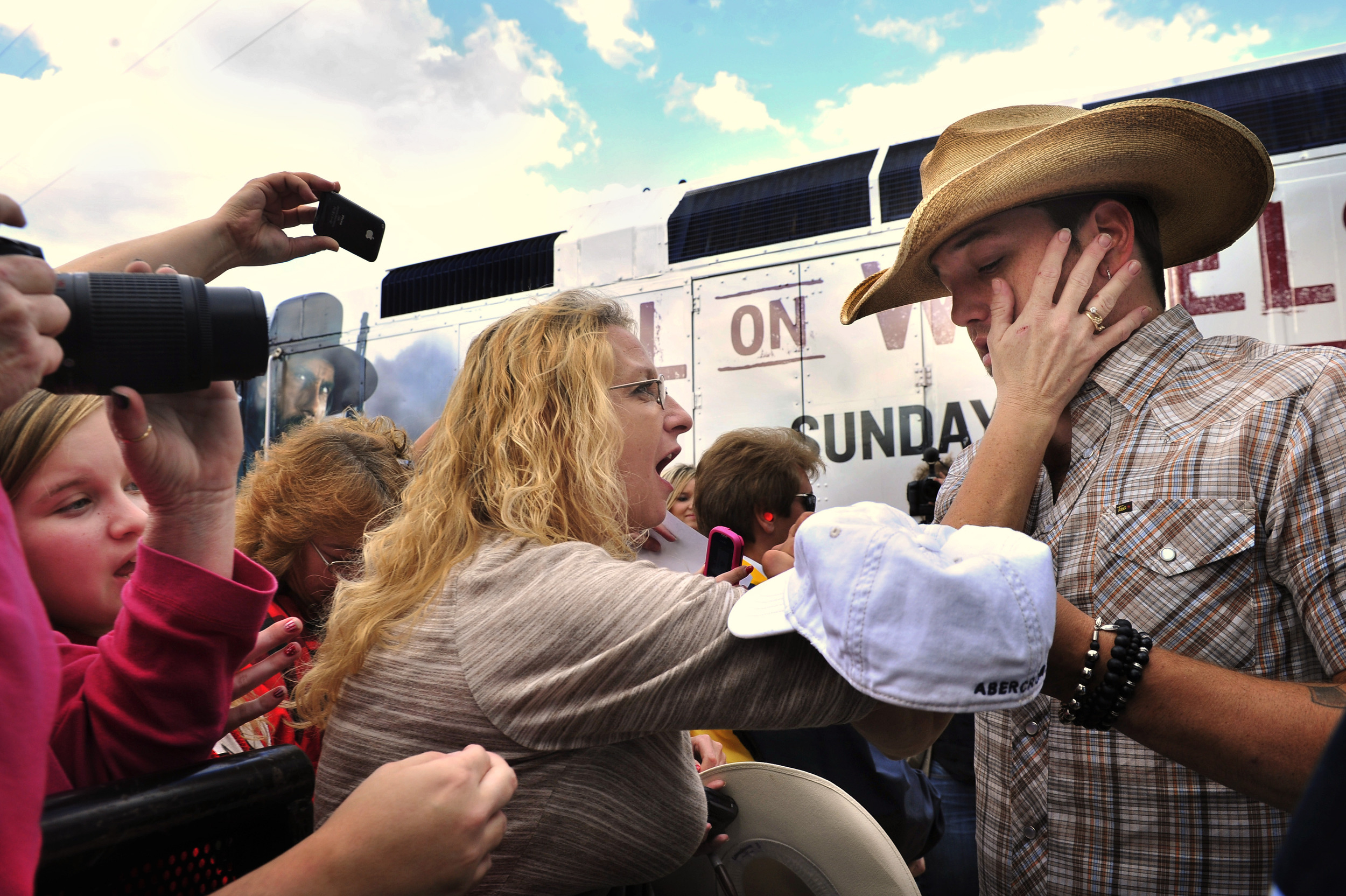 A fan touches Jason Aldean as he signs autographs for fans after a free concert at the riverfront downtown in Nashville, Tenn.