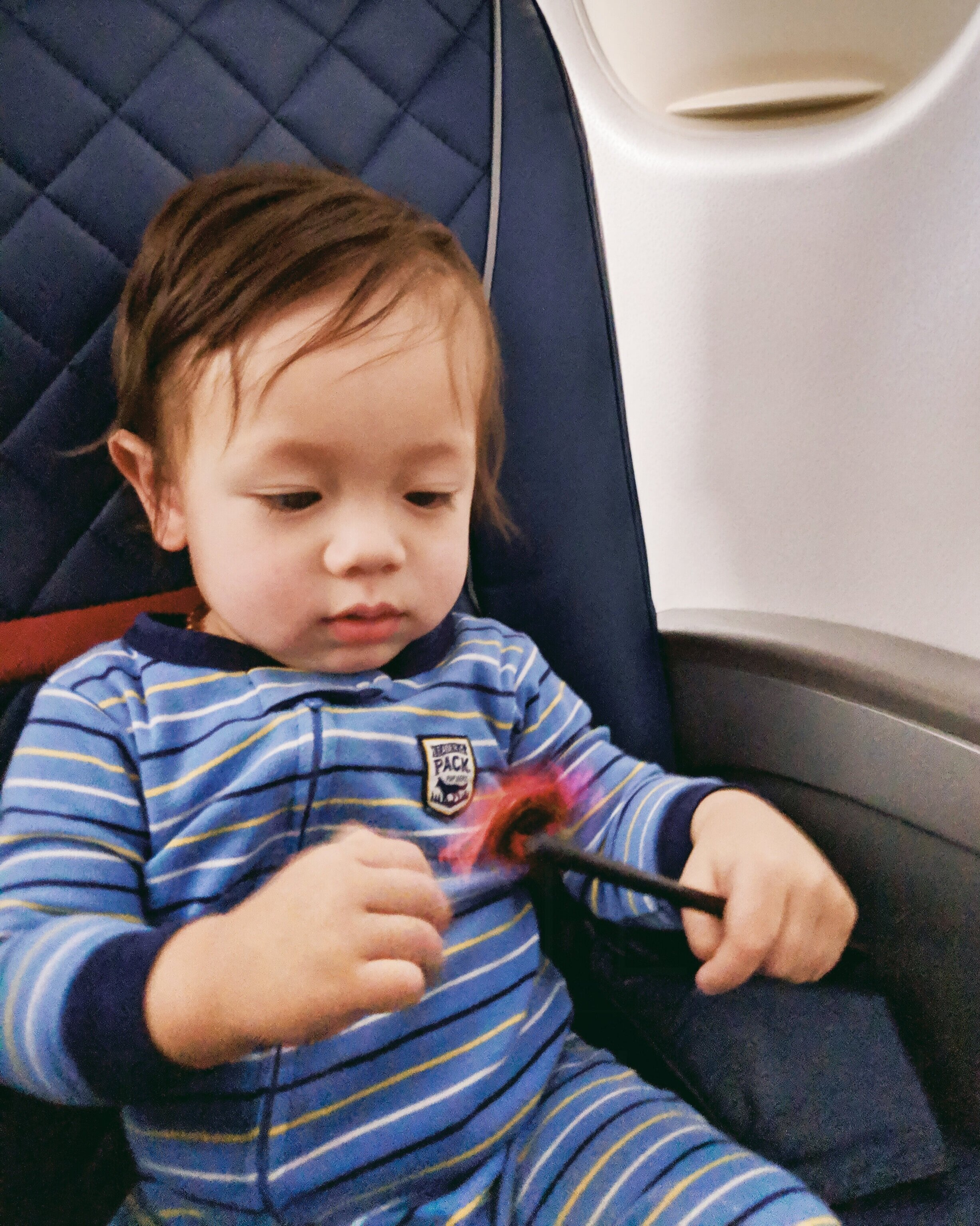 Orlo playing with a pinwheel from the Travel Toyz pack for an entire flight