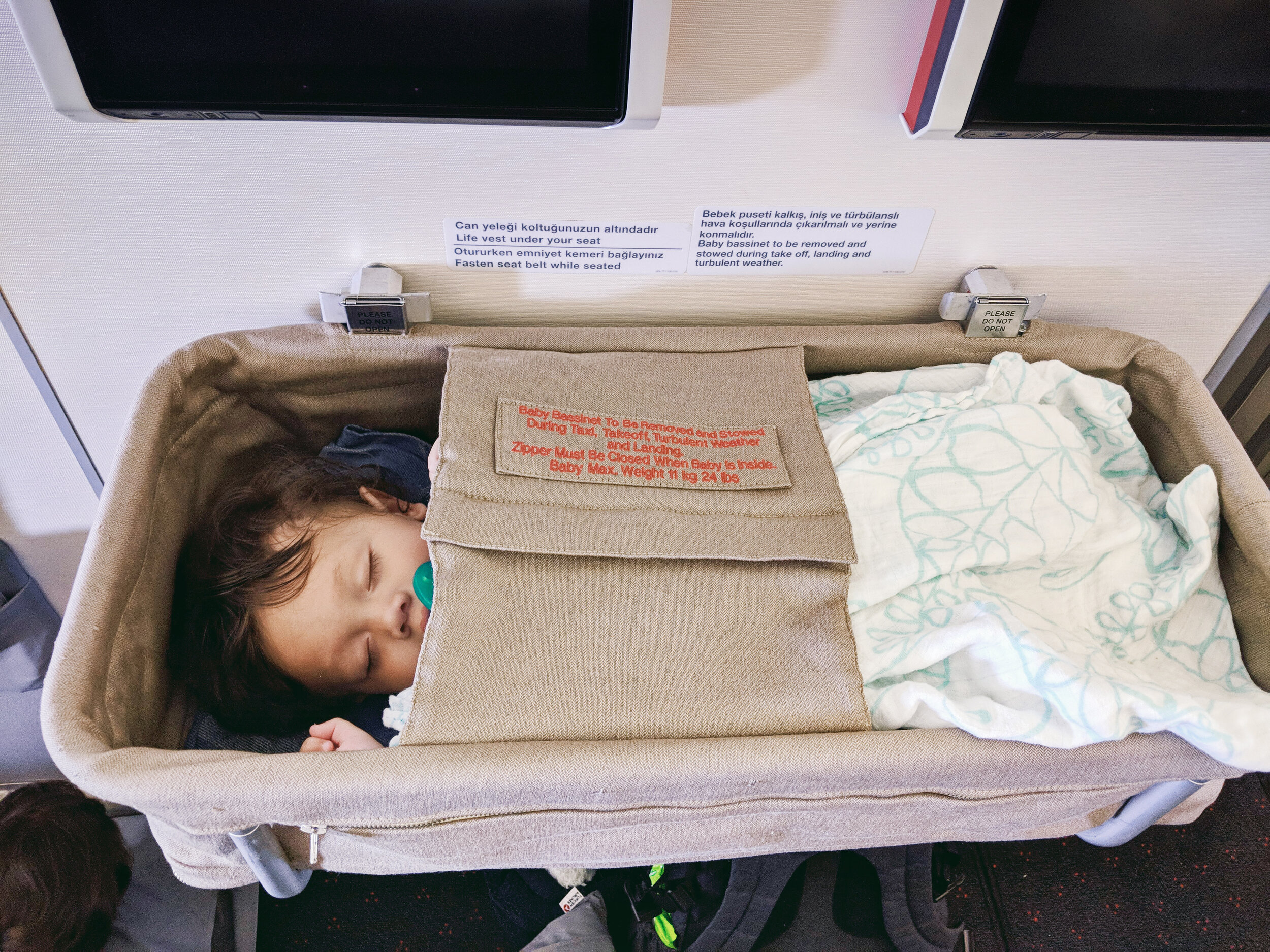 Orlo (6 months old) sleeping in airplane baby bassinet on Turkish Airlines