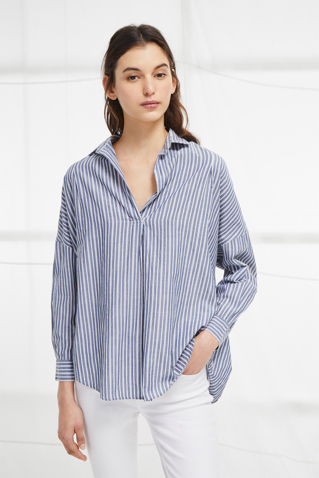 TATUS STRIPE POP OVER SHIRT - The Tatus Stripe Pop Over Shirt is a fresh update for your separates. The oversized pull-over shirt has a casual fit, with a relaxed collar and V-neckline. Long sleeves with large cuffs can be rolled up for more relaxed styling. The shirt is finished with a crisp blue and white stripe, adding colour to the understated piece, which will pair perfectly with shorts on warmer days.