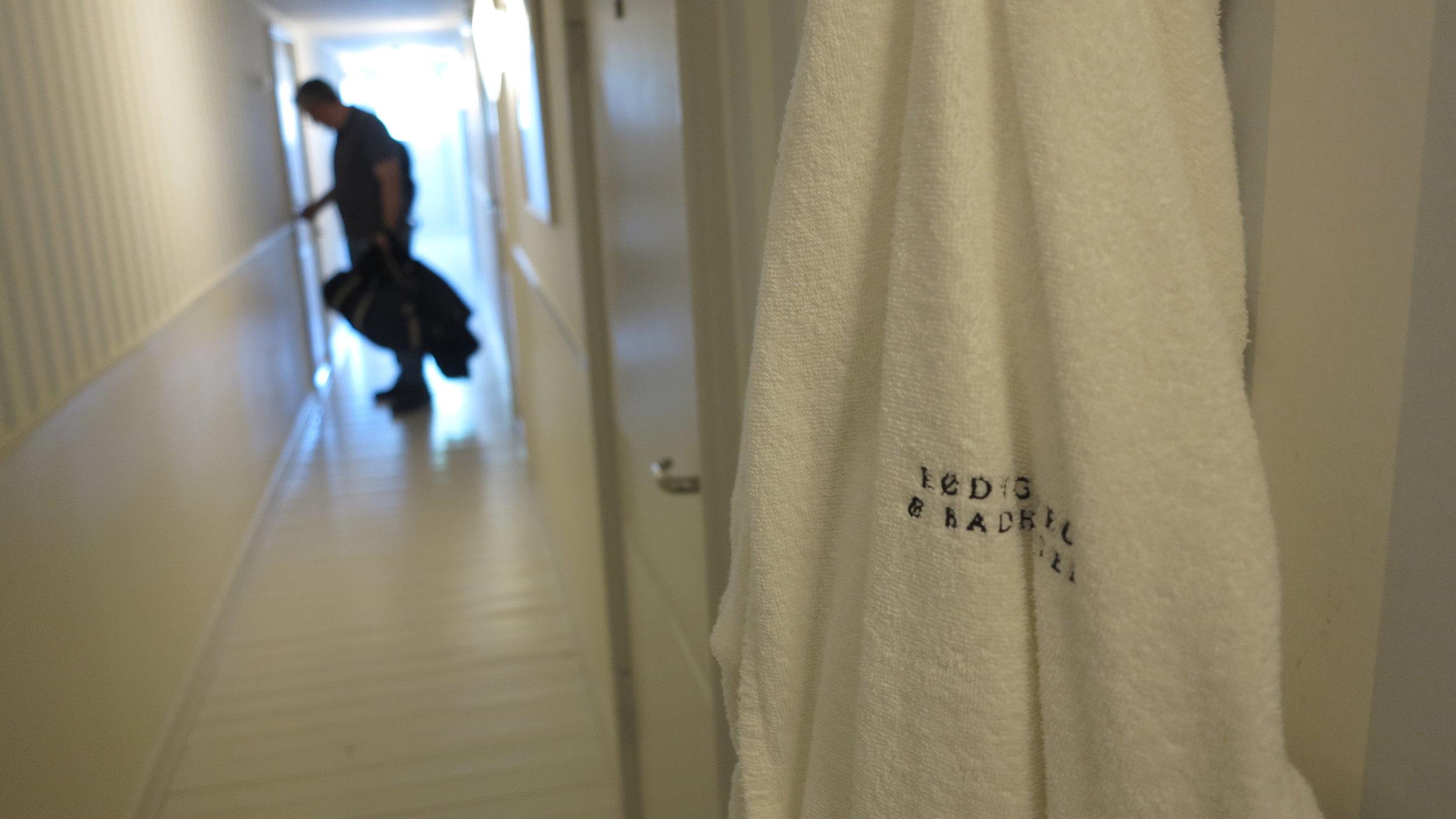 Zwischen den Zimmertüren hängen weiße Bademäntel für den schnellen Gang zum Meer