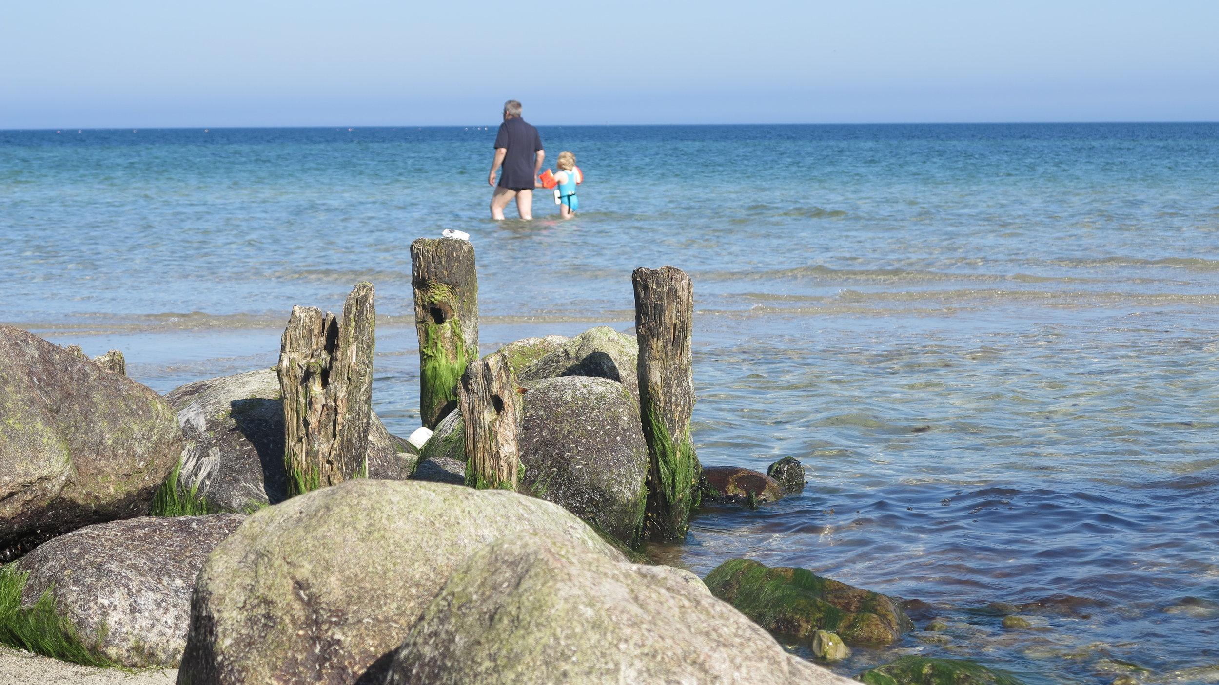 Familienfreundlicher Strandabschnitt mit großen und kleinen Steinen, aber immer auch mal einem Plätzchen mit feinem Sand – und vor allem: einem sanften, flachen Weg ins Wasser