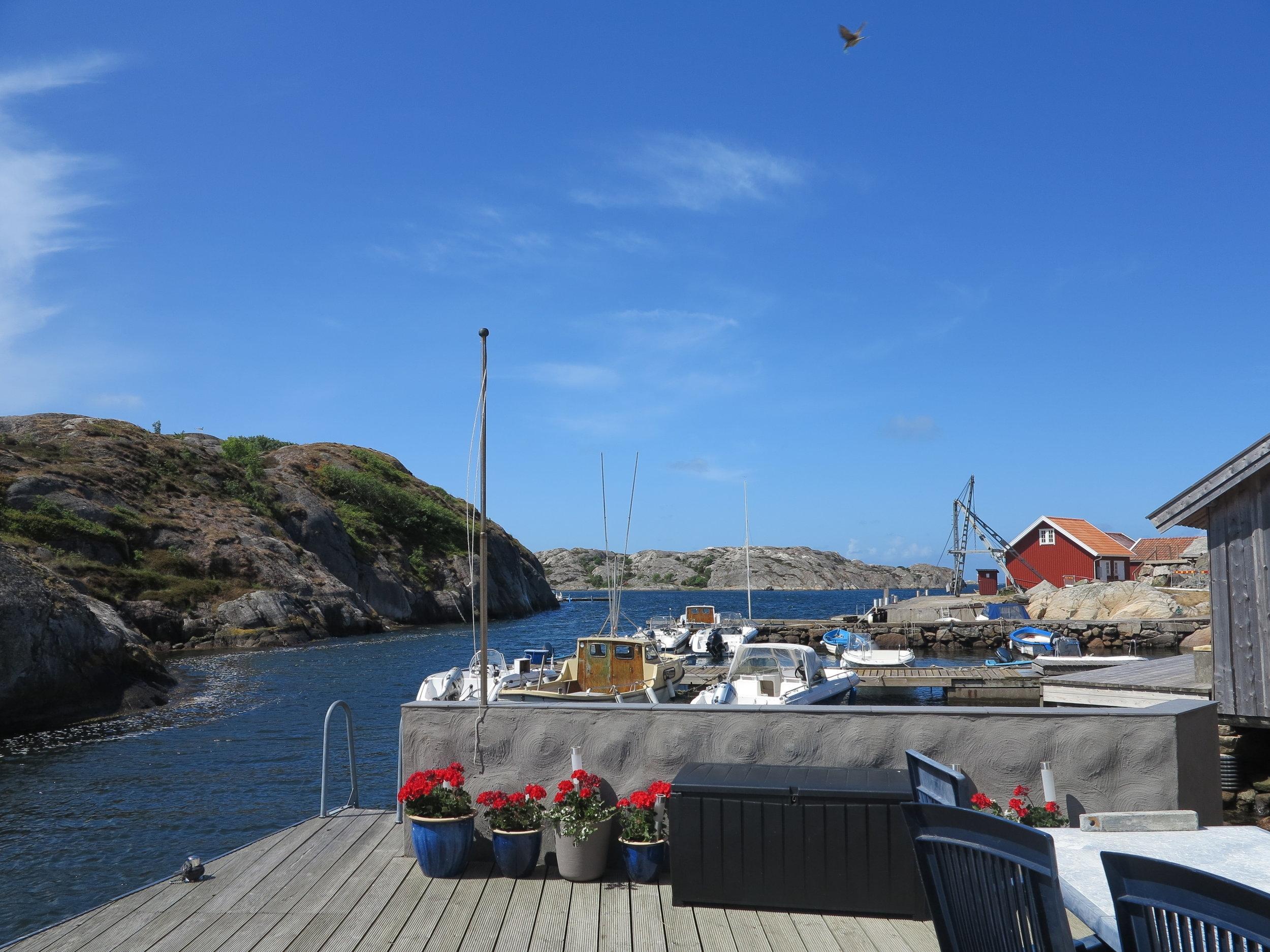 Unser Blick auf glattgeschliffene Felsrücken, Boote und einen strahlend blauen Sommerhimmel