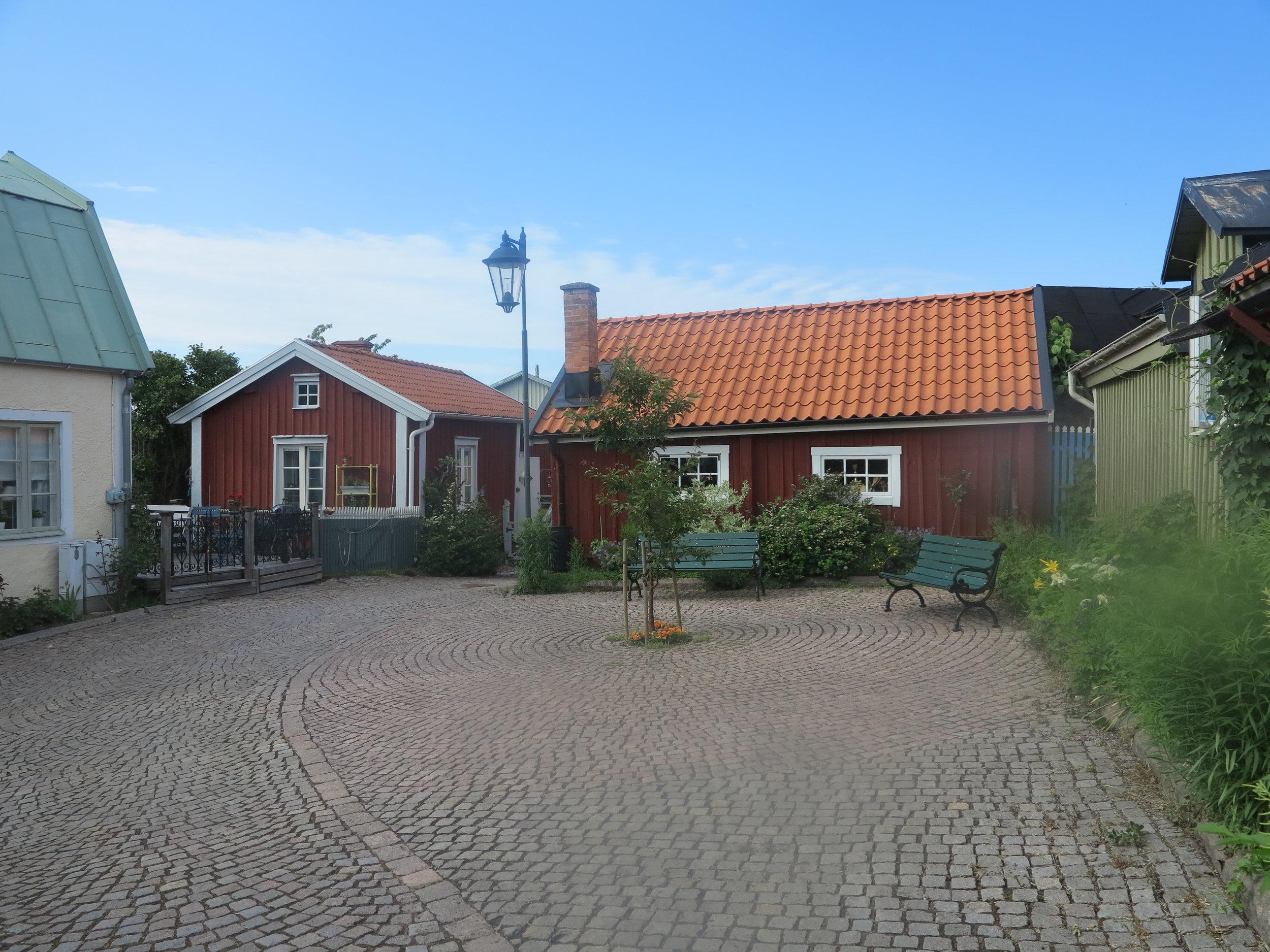 Ein kleiner Platz zwischen roten Holzhäusern. Wenn man dort auf einer der Bänke sitzt, fühlt es sich an, als wäre die Zeit stehengeblieben