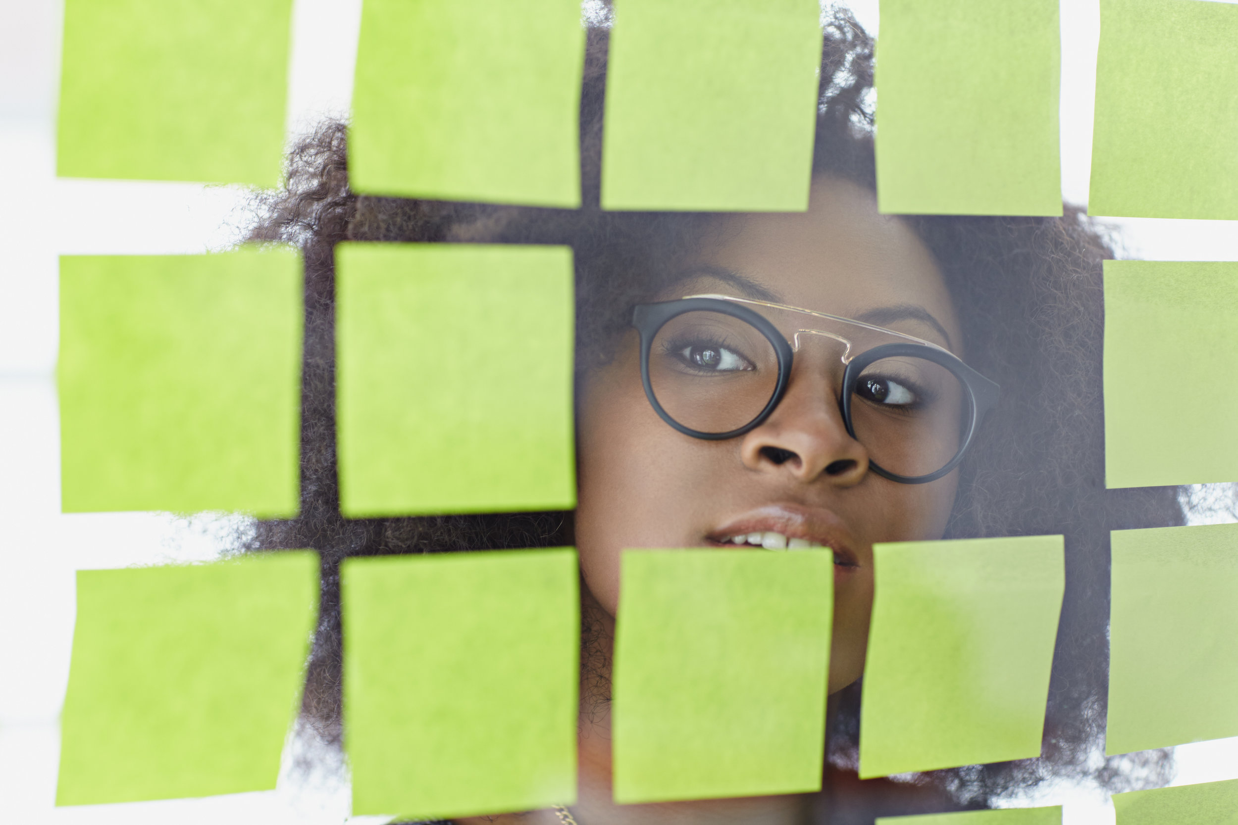 photodune-15095119-portrait-of-a-business-woman-with-an-afro-behind-sticky-notes-in-bright-glass-office-xxl.jpg